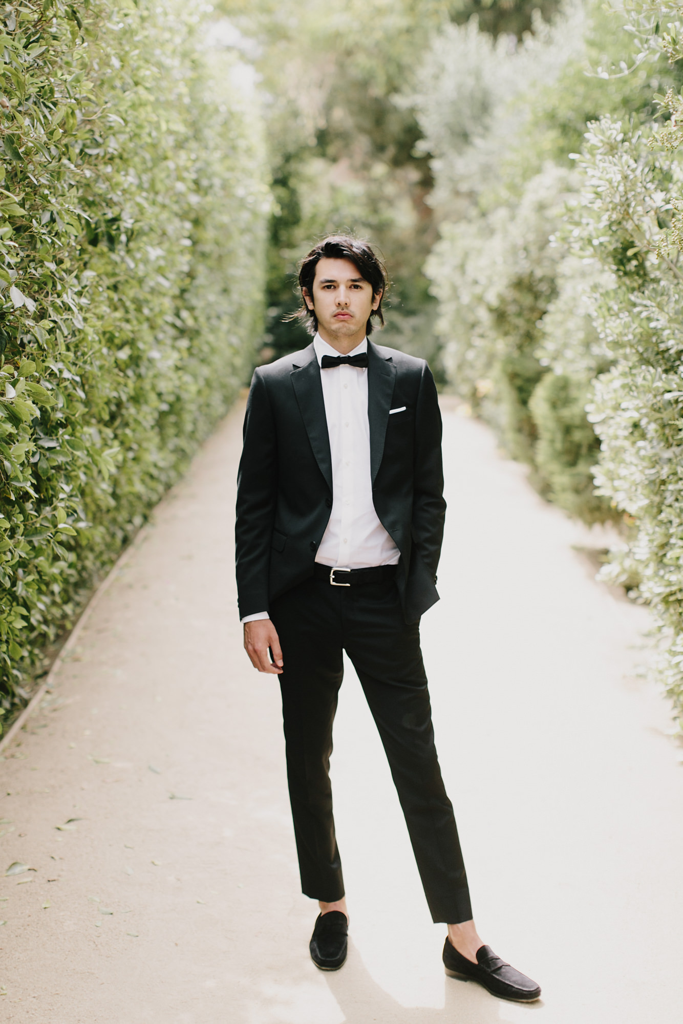 Portrait of groom in black suit, bow tie and capri pants by James Moes