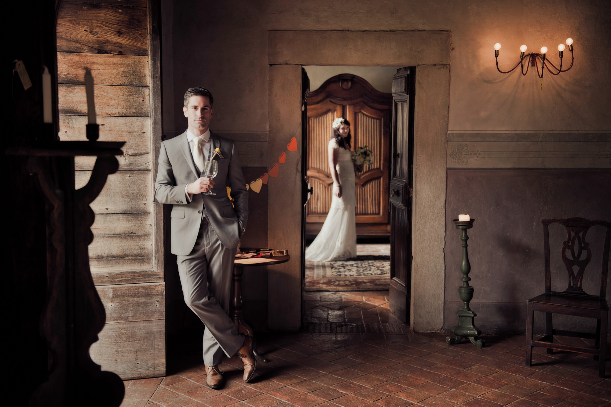 Groom in grey suit with bride behind in doorway  -  Studio Impressions Photography
