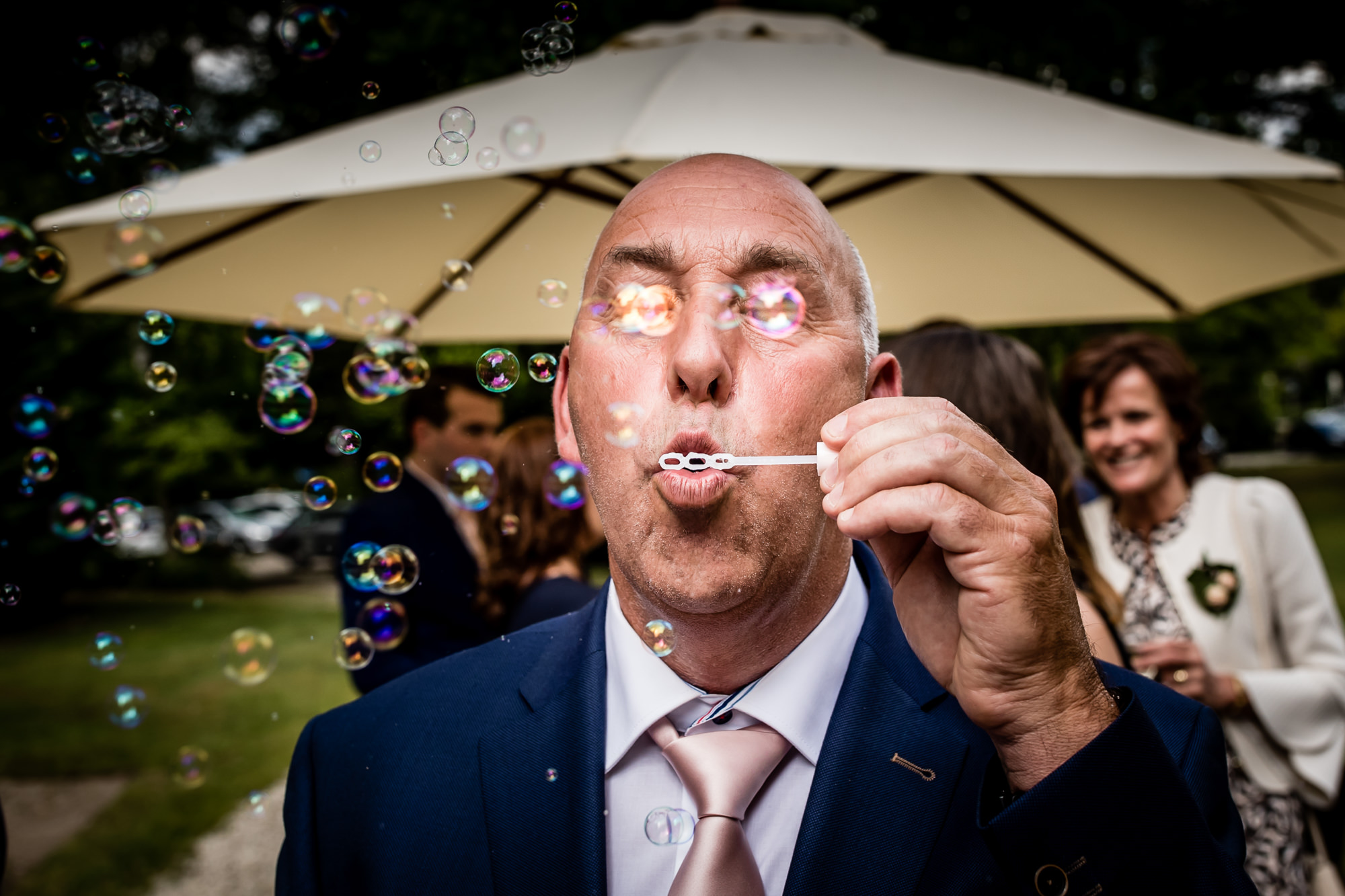 Father of the bride blows bubble in front of his eyes - photo by Eppel Photography