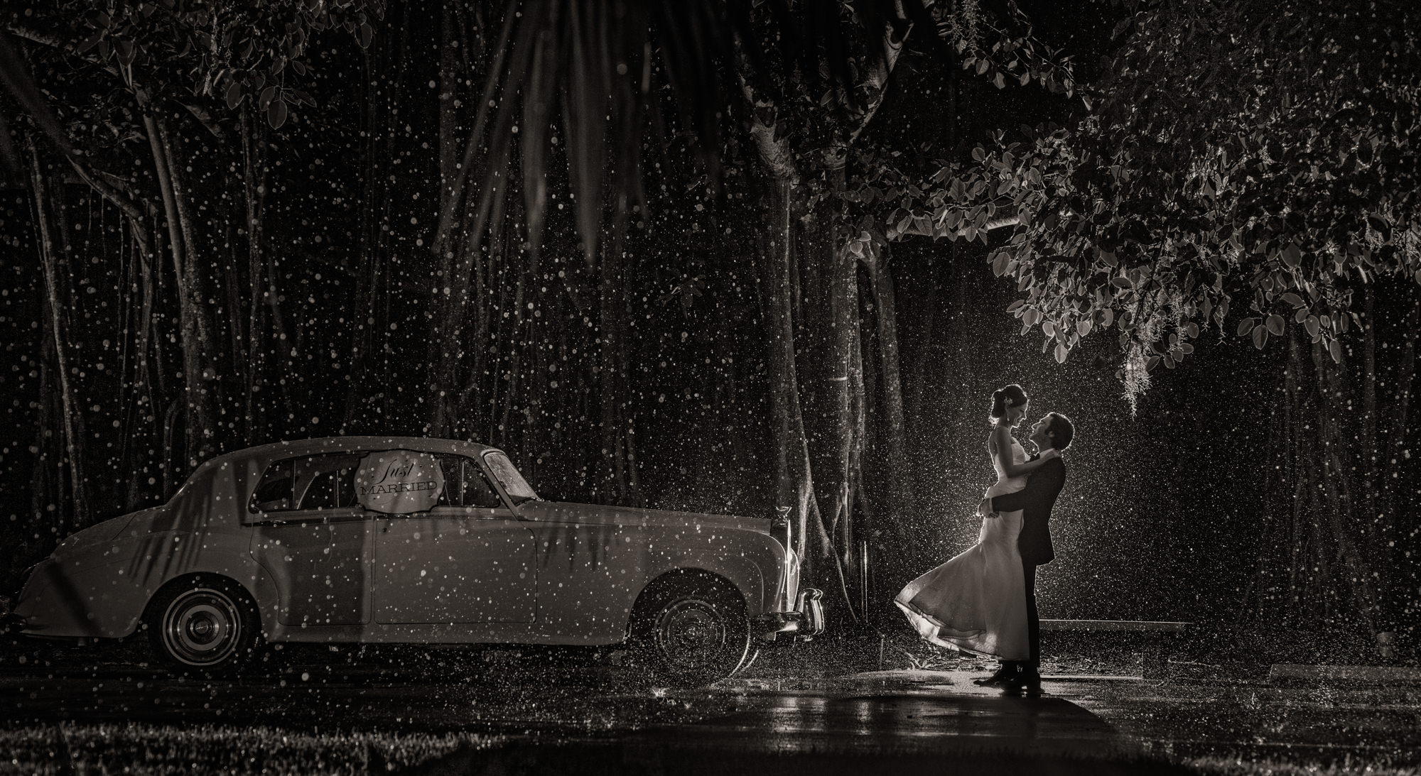 Photo of groom lifting bride up in the pouring rain by Roberto Valenzuela