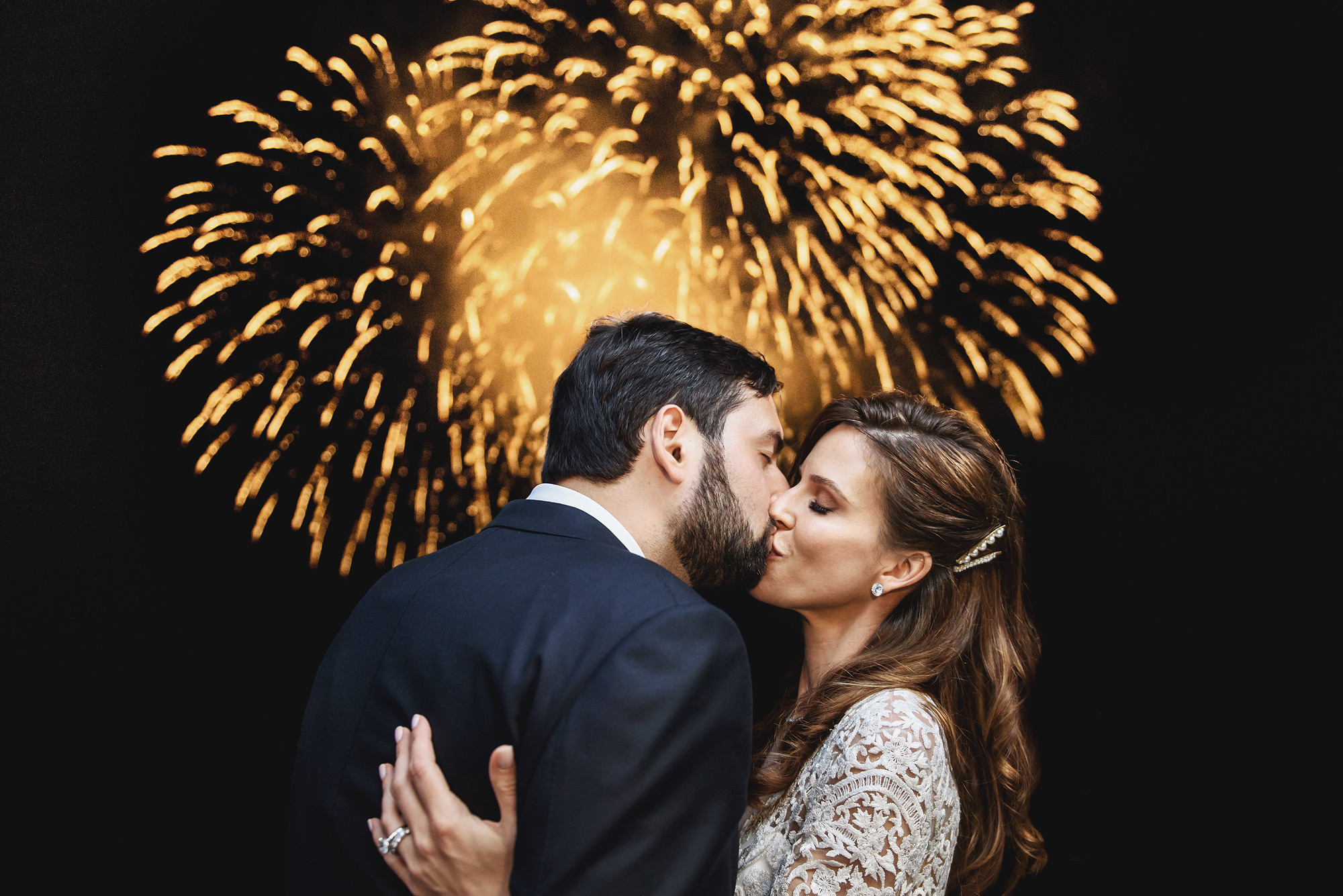 Couple kissing against fireworks - photo by Ross Harvey