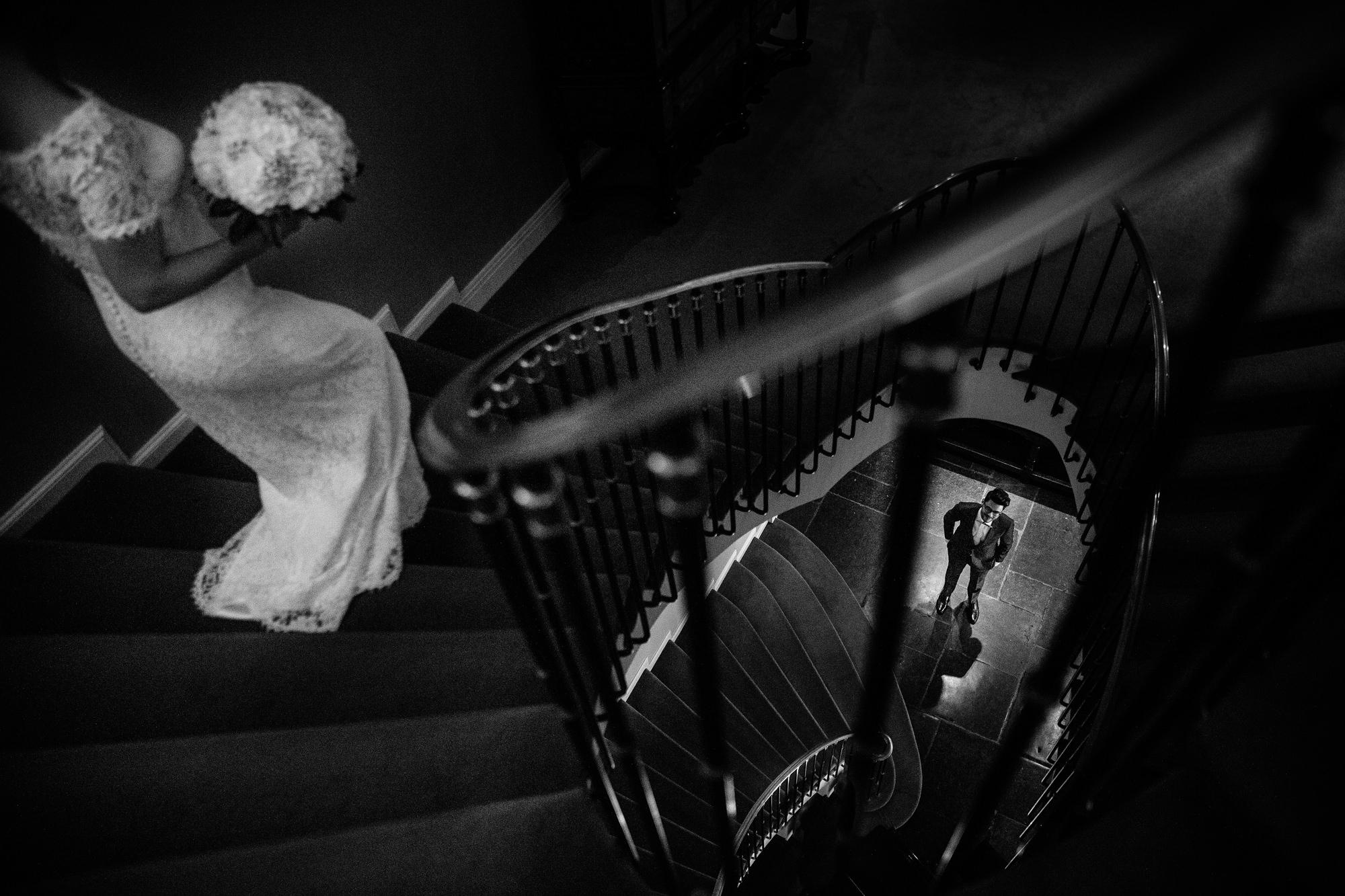 First look bride descends stairs to groom Yves Schepers Belgium wedding photographers