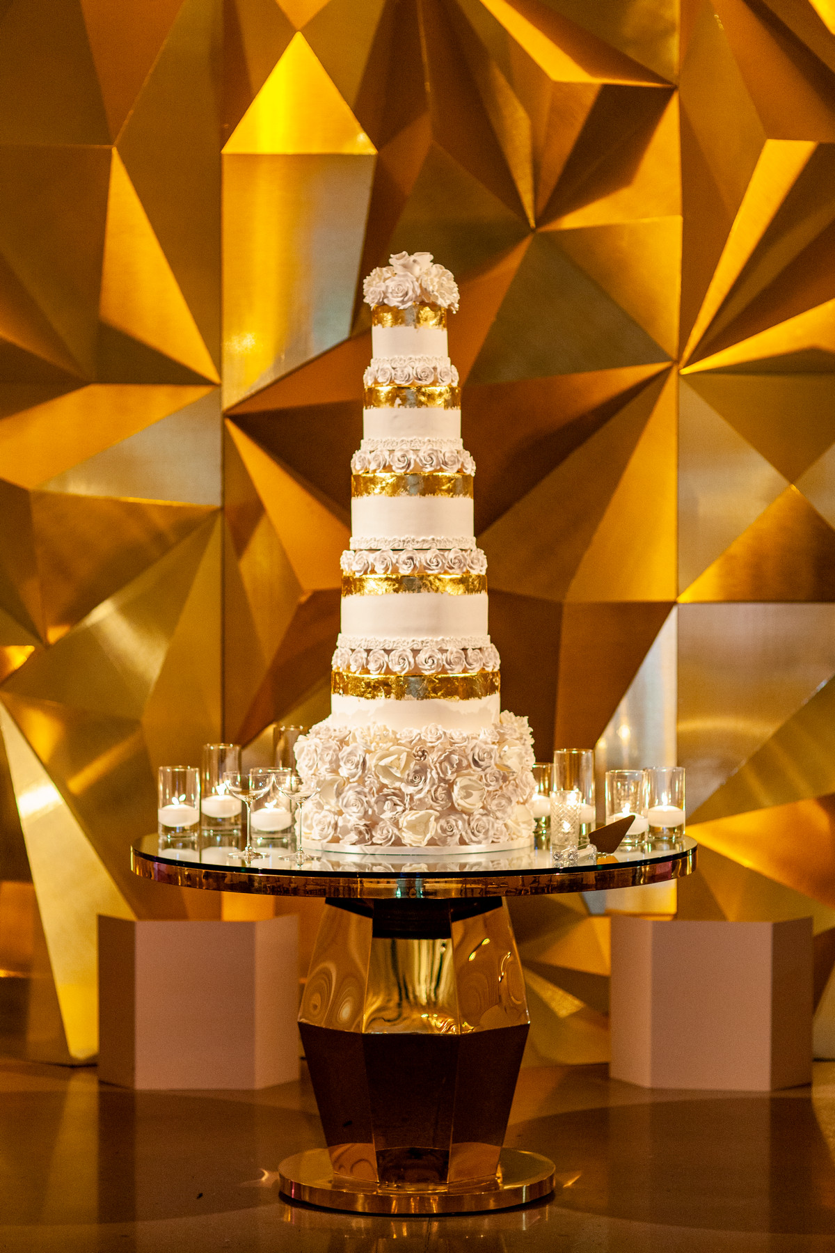 Six tier wedding cake with gold ribbon and white roses -John and Joseph Photography