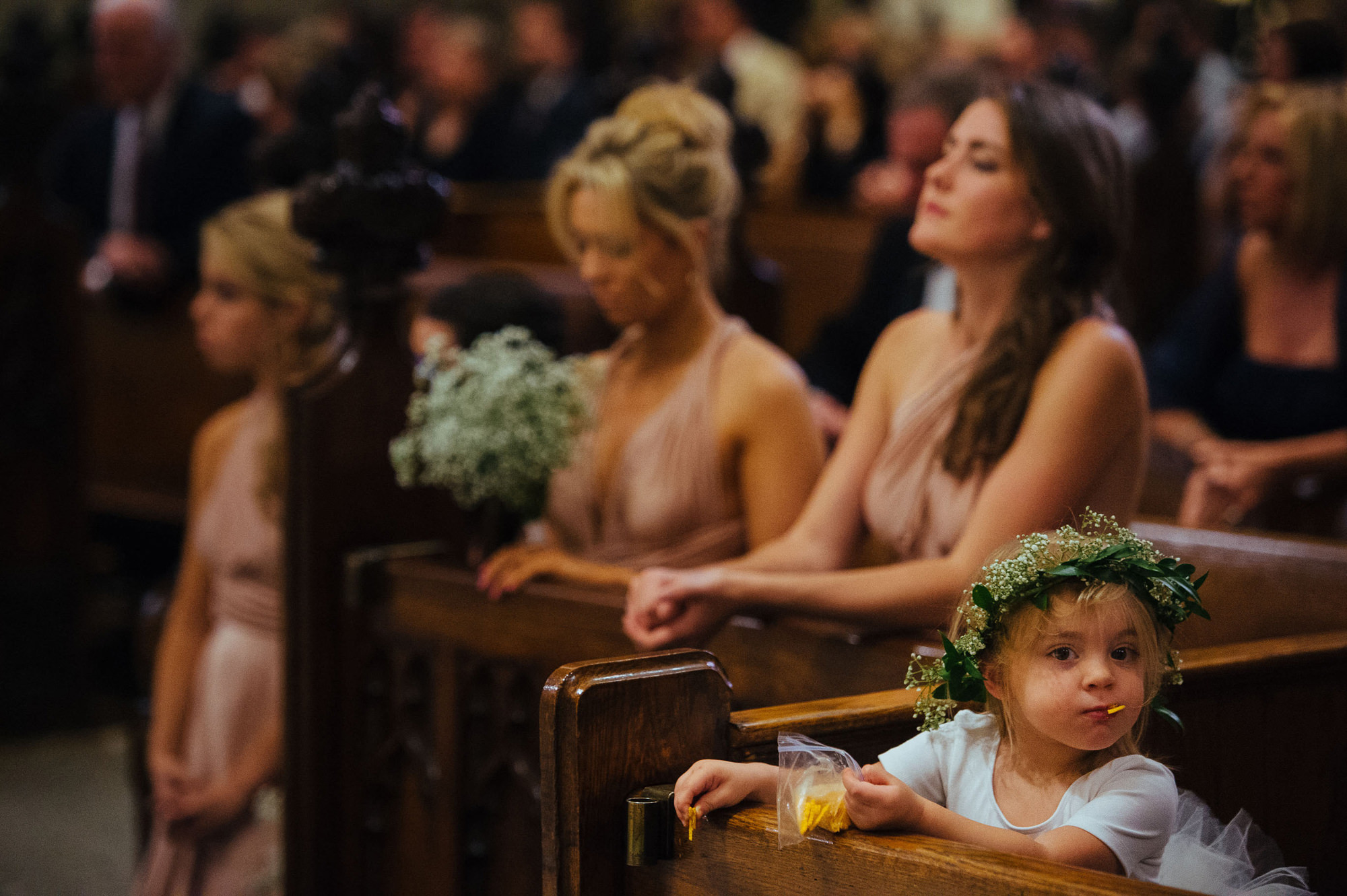 Cute photo of flower girl in floral crown eating snacks at church ceremony, by The Brenizers