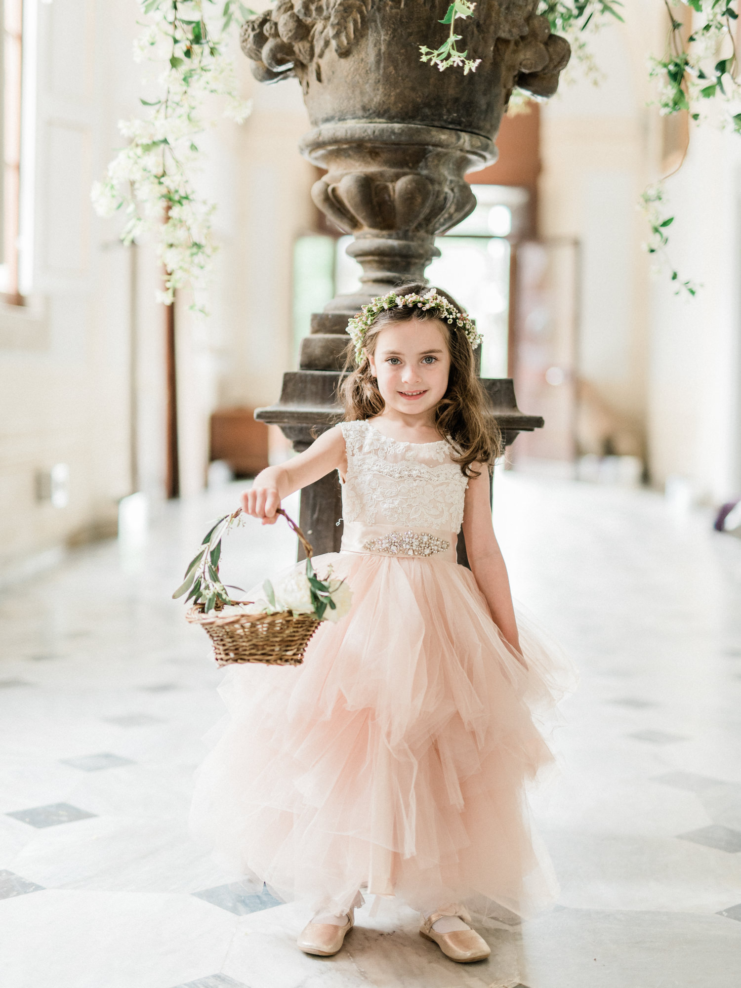 Flower girl in blush tulle dress with basket wearing floral crown - photo by Gianluca Adoviaso Photography