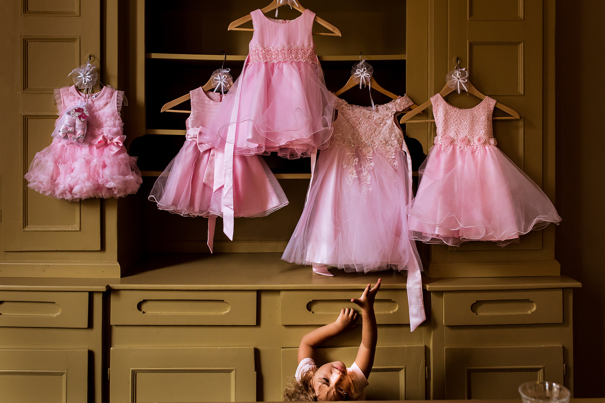 Little girl reaching for hanging pink dresses photo by Fotobelle: Isabelle Hattink