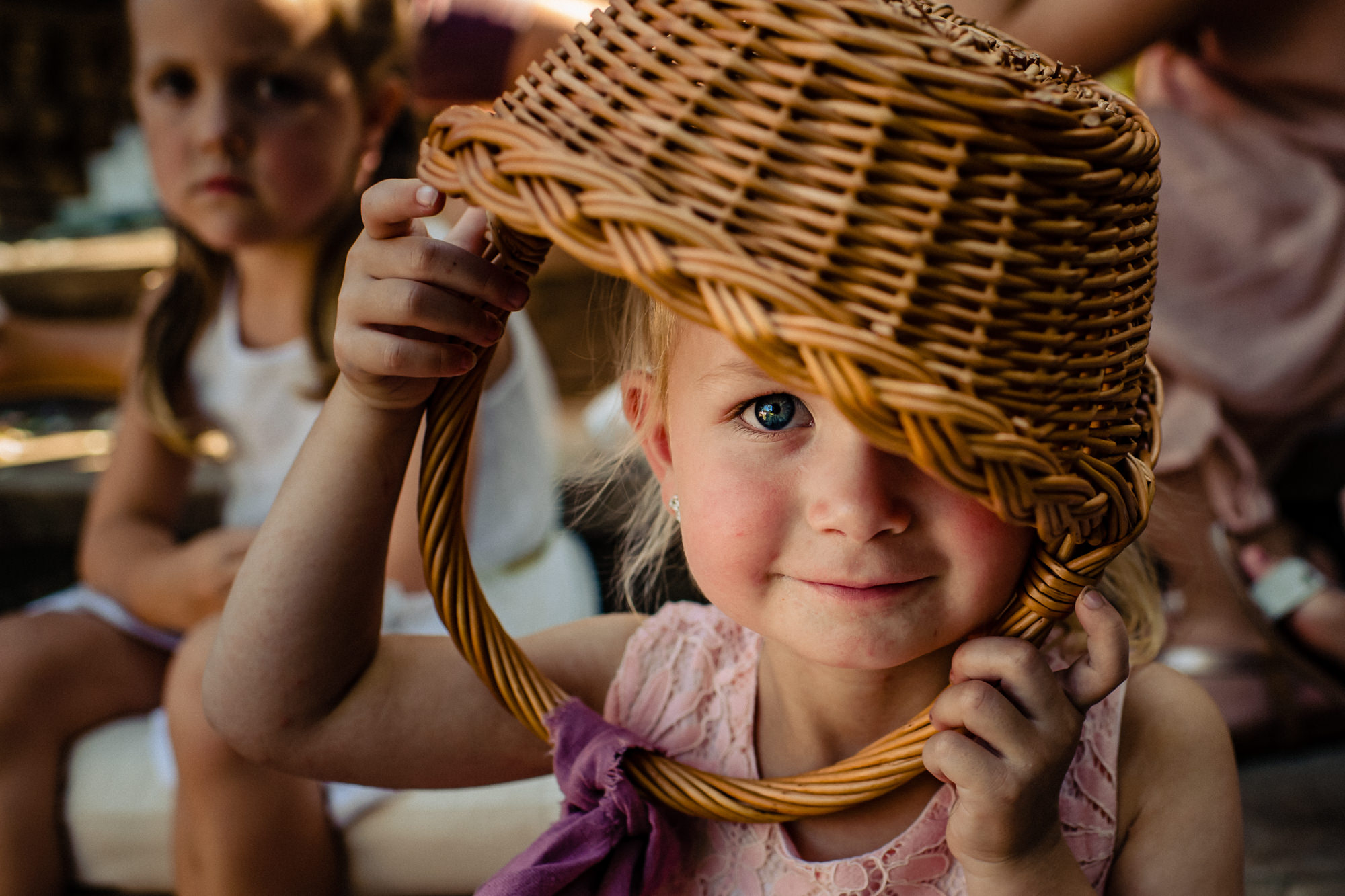 Flower girls face under her empty basket - photo by Eppel Photography