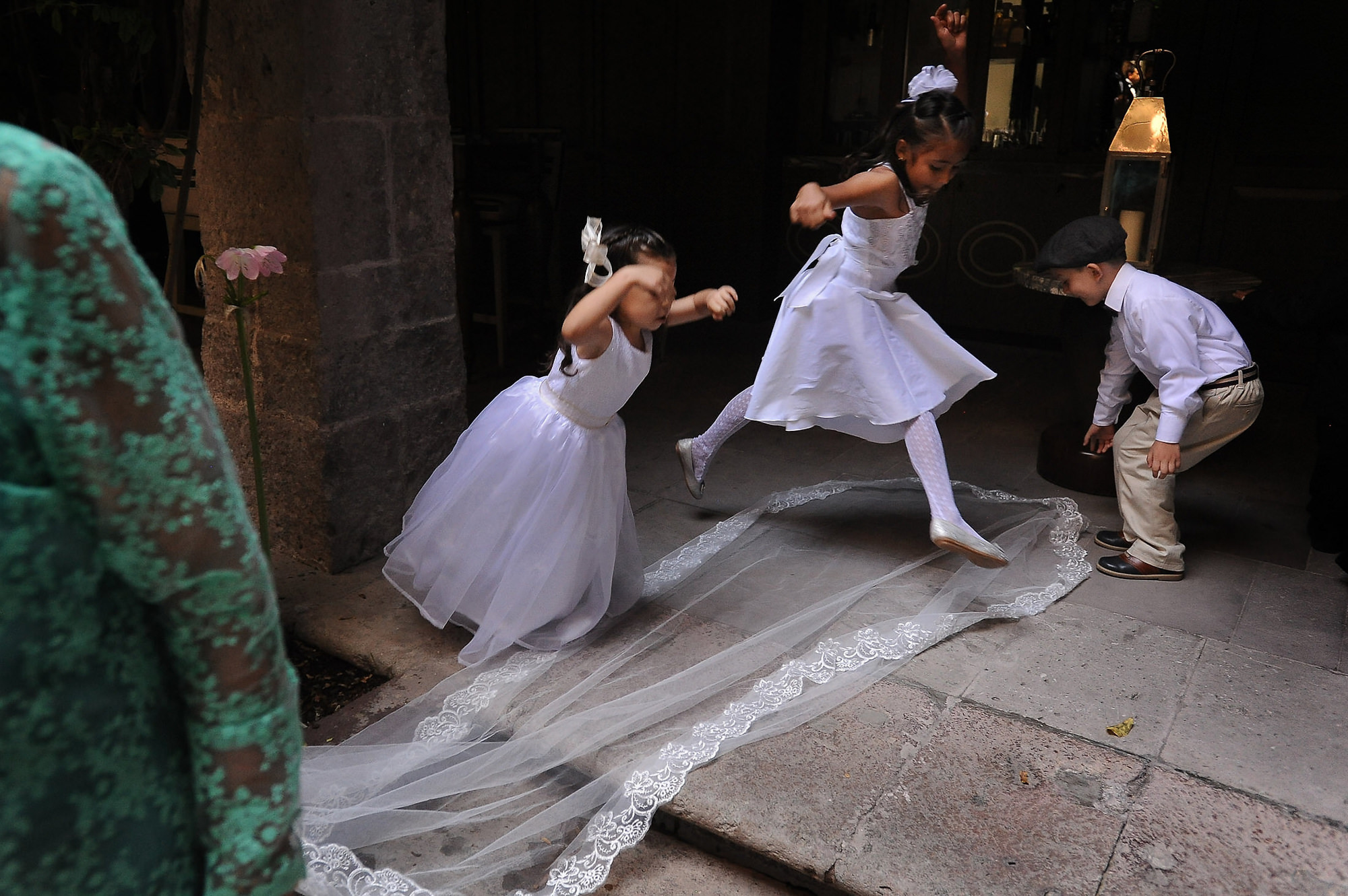 Flower girls jumping over brail veil and train - photo by Daniel Aguilar