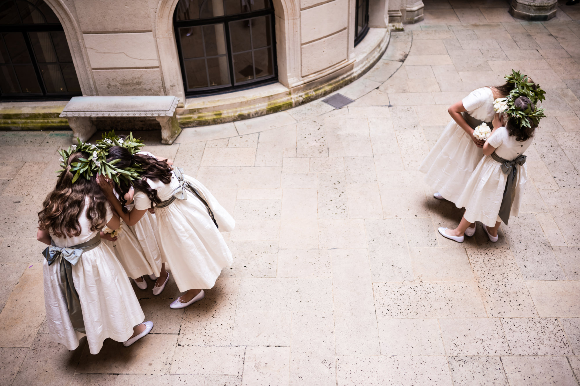 Flower girls whispering in courtyard photo by Cliff Mautner