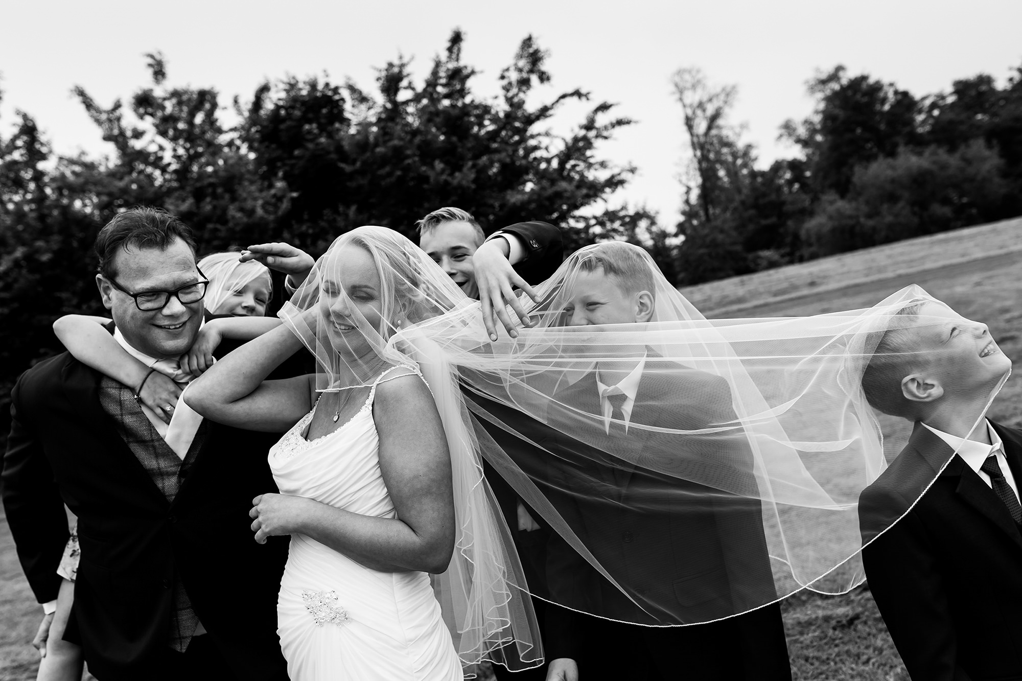 Bride and groom with family under veil photo by Fotobelle: Isabelle Hattink