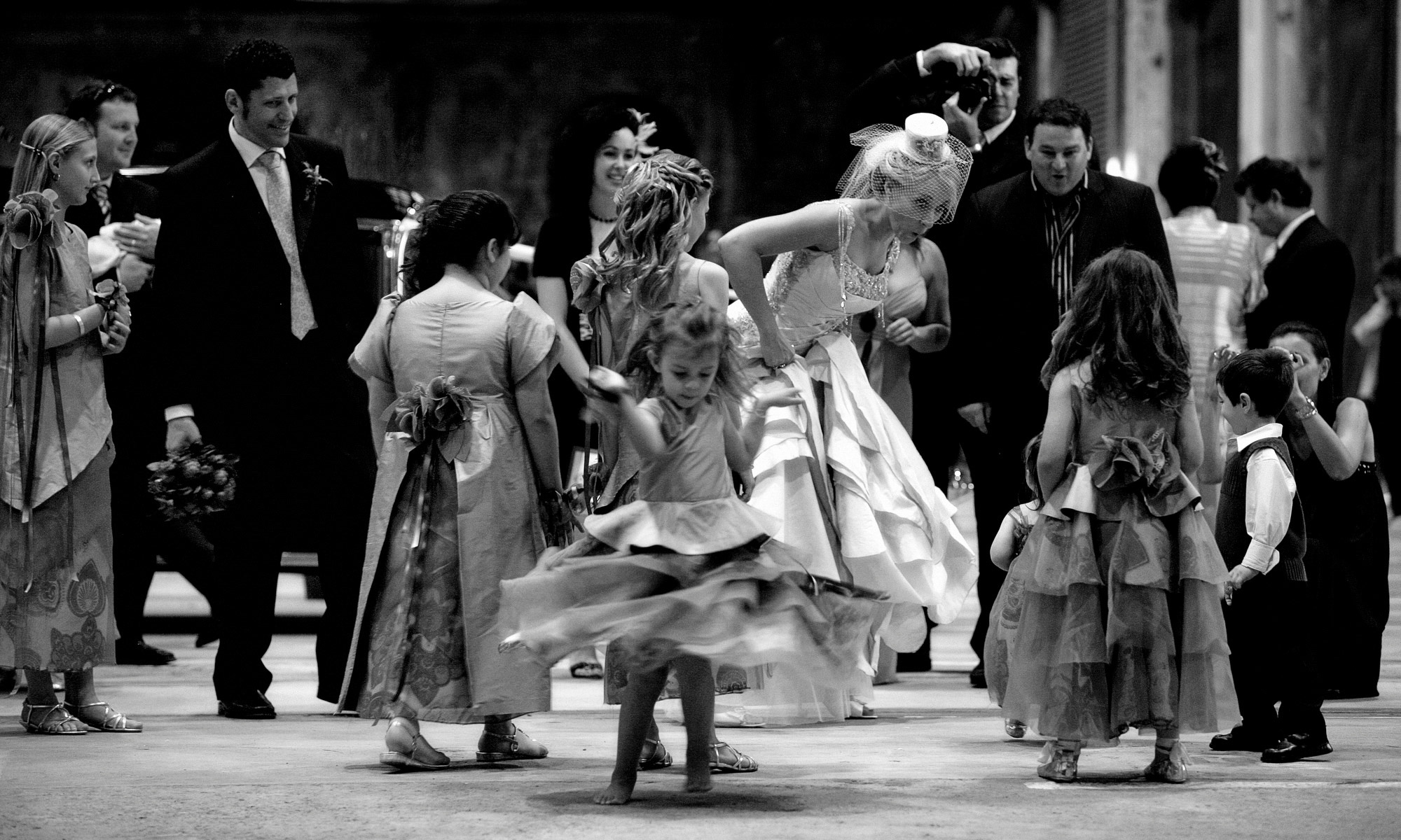 Fun bride with fascinator dancing with kids photo by Jerry Ghionis