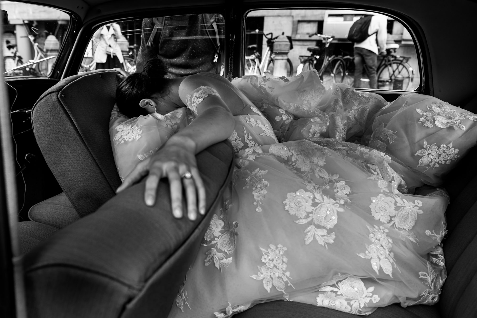 Bride burying face in gown in limo photo by Fotobelle: Isabelle Hattink