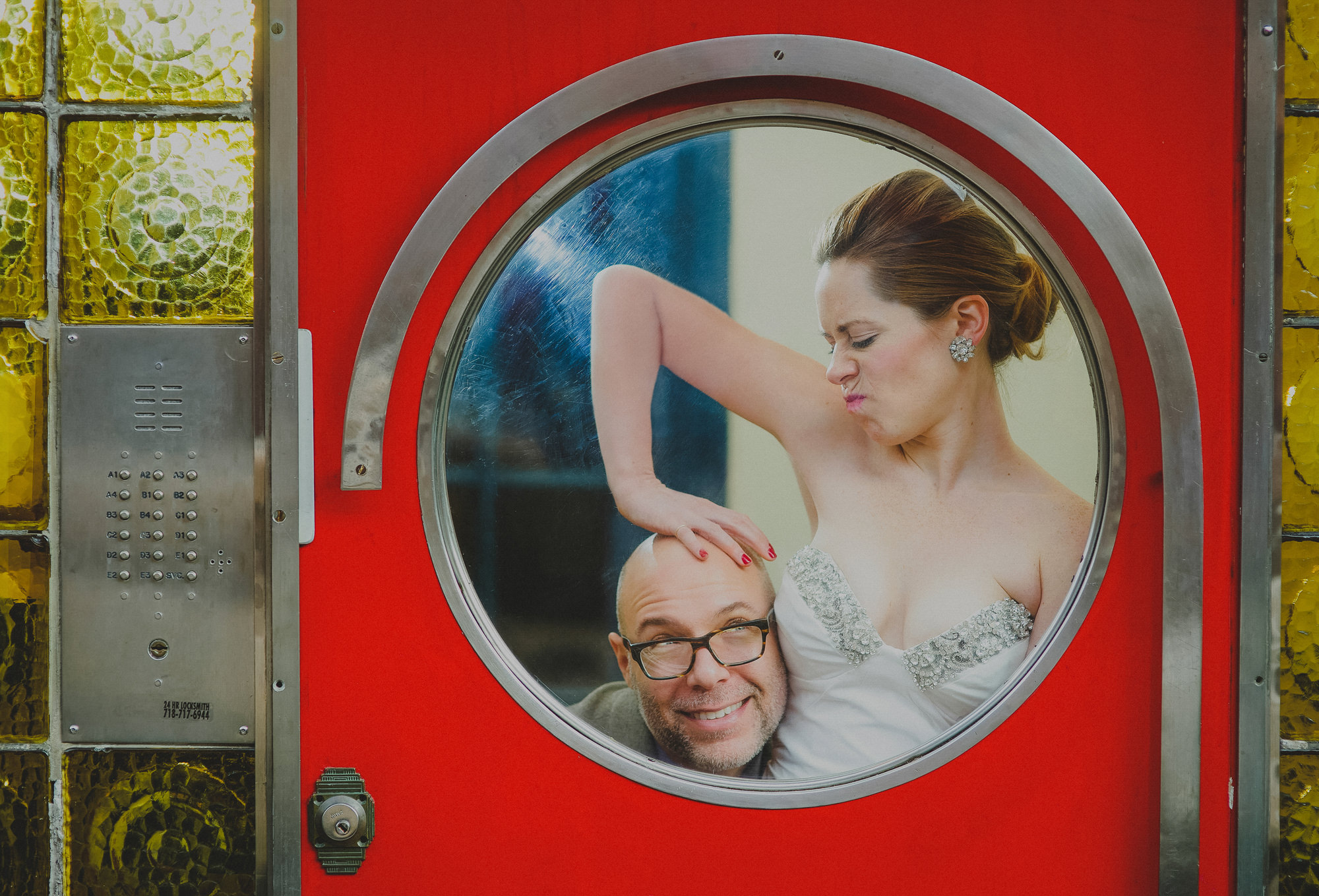 Cute couple bride pressing groom's head down through red door window, by the Brenizers