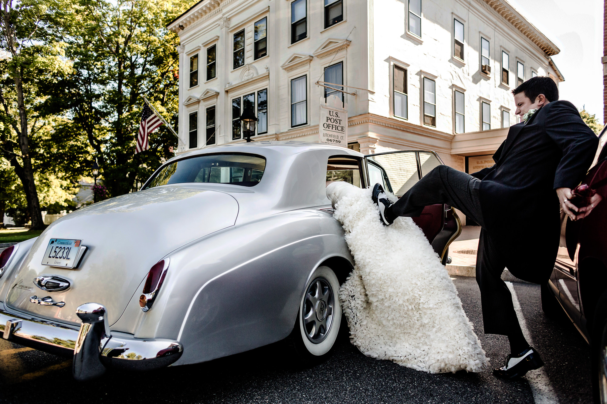 Funny photo of groom pushing bride into car with his foot by Jag Studios