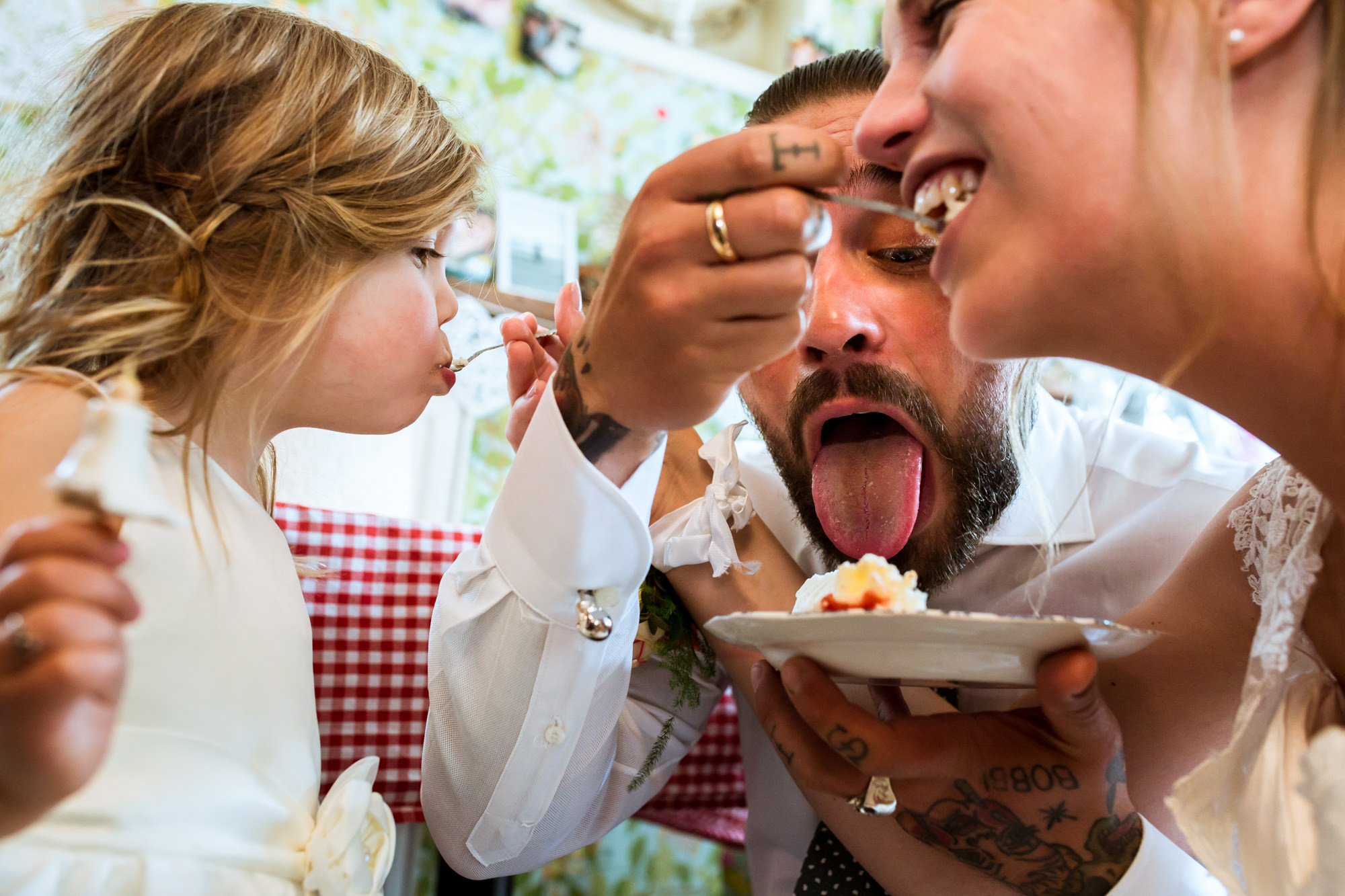 Layered shot of bride, groom and child eating cake photo by Fotobelle: Isabelle Hattink