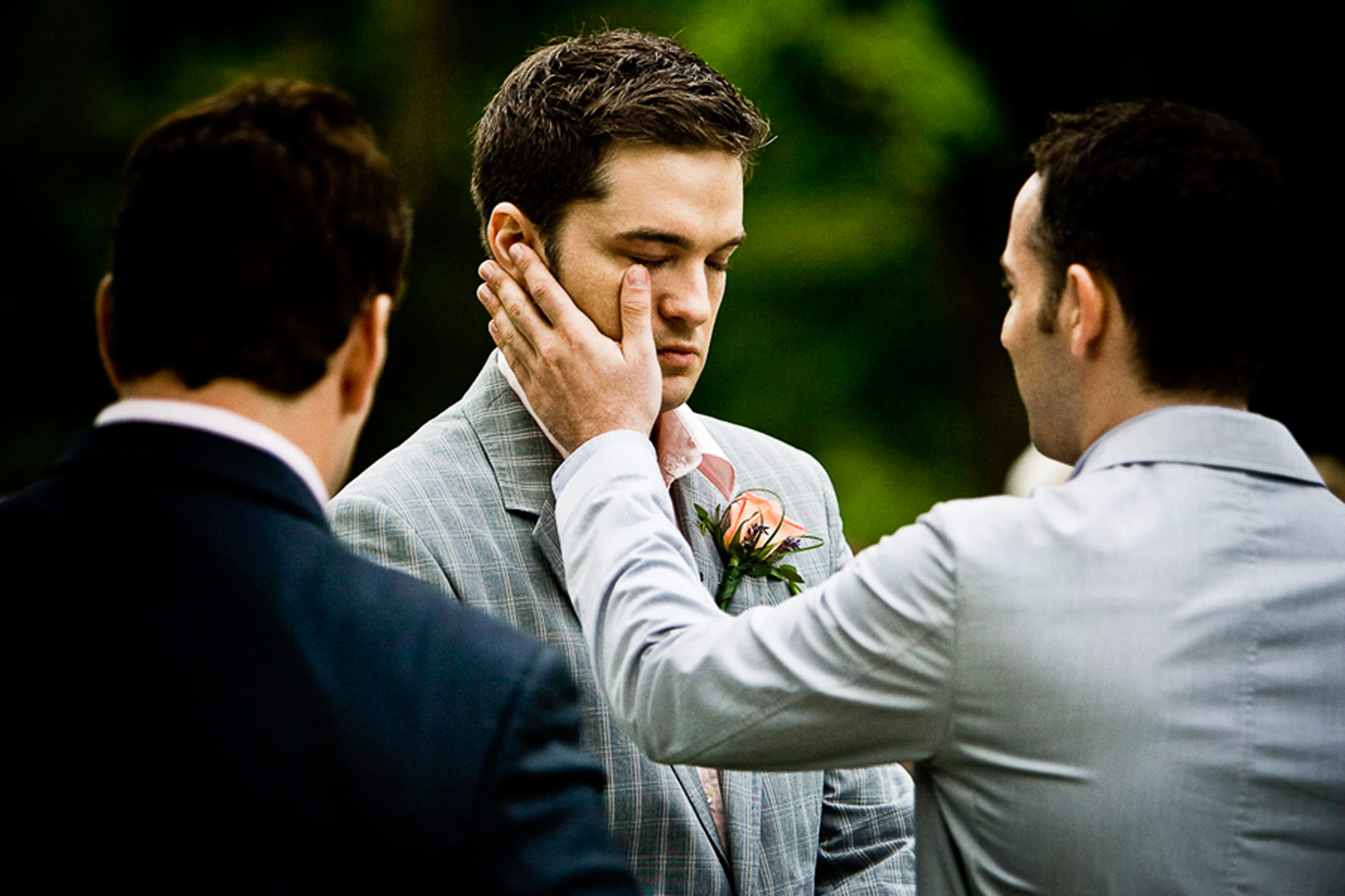 Groom wipes away groom's tears during ceremony photo by Jag Studios