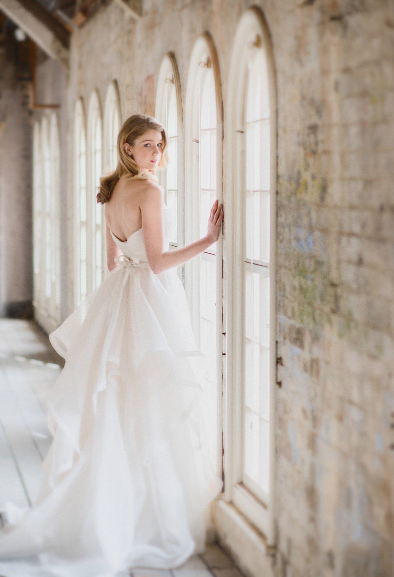 Fashionable bride wearing white backless dress with ruffled train  -  Studio Impressions Photography