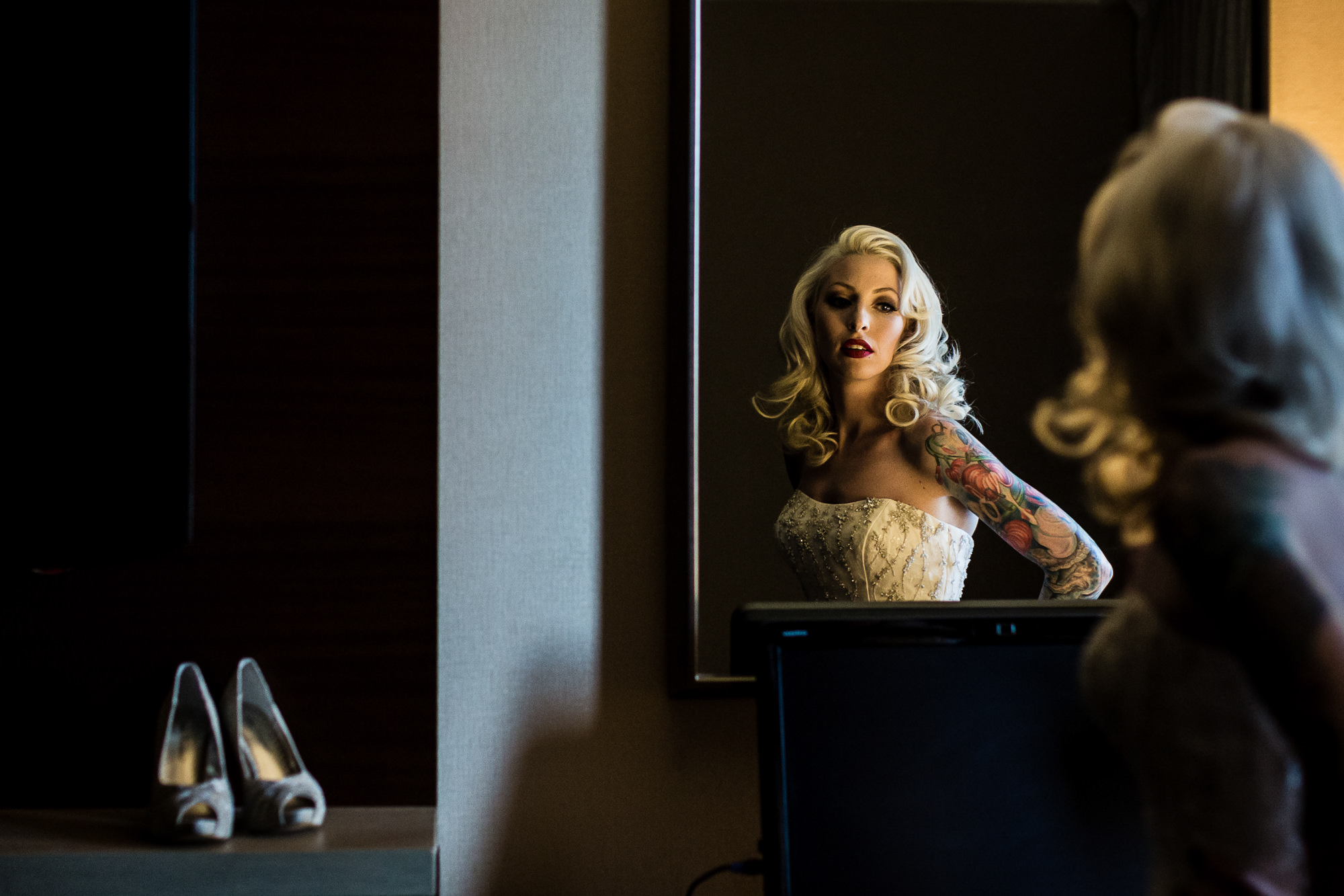 Glamourous bride with tattoos in mirror - photo by Jag Studios