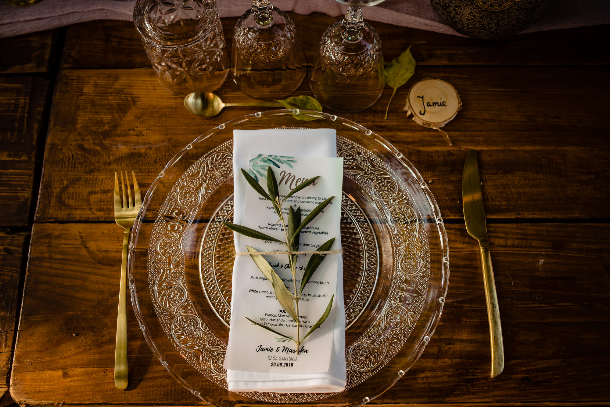 Glass charger, gold flatware, menu with bay leaves - photo by Eppel Photography