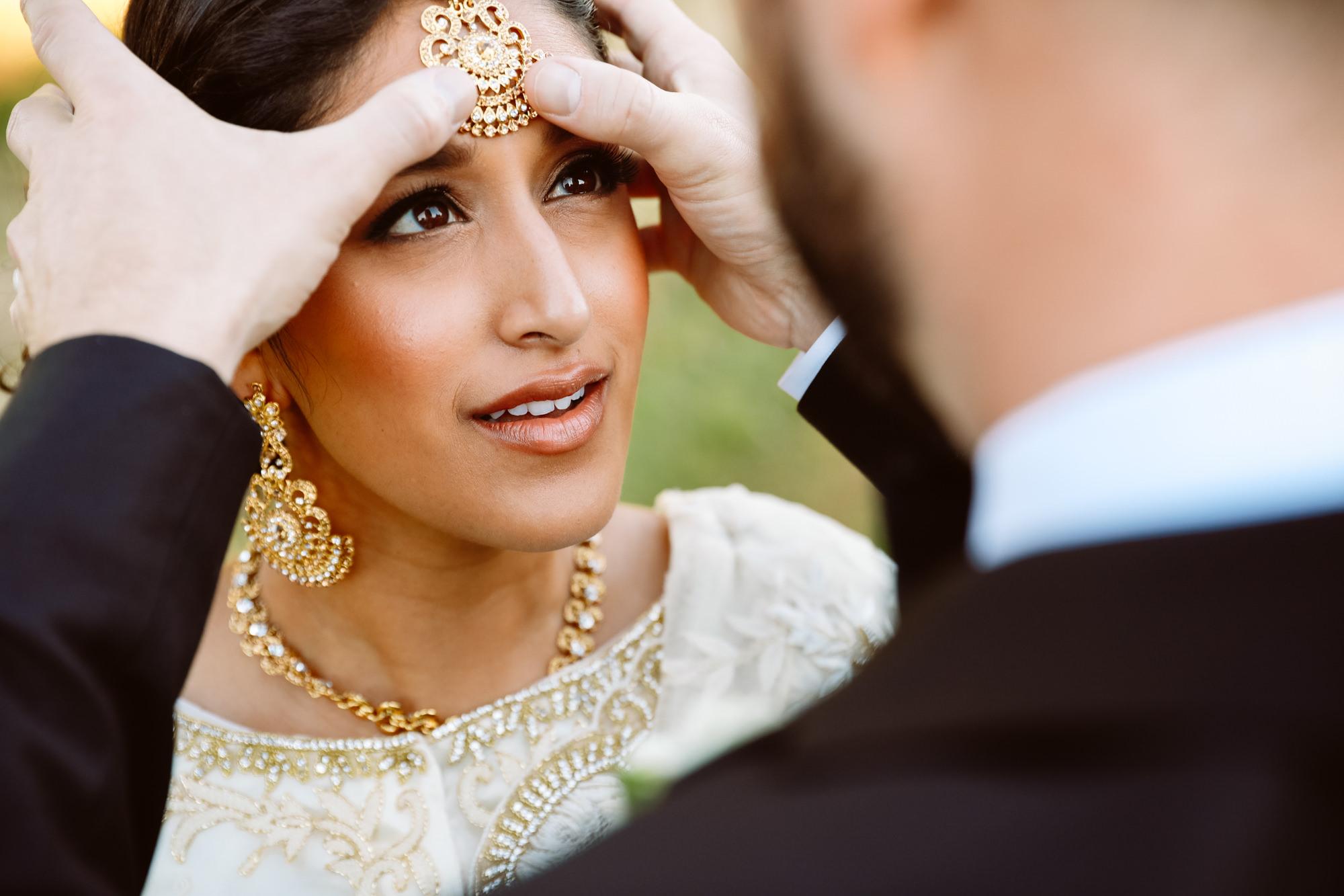 Groom adjusting bride's golden tikka  - Jessica Hill Photography