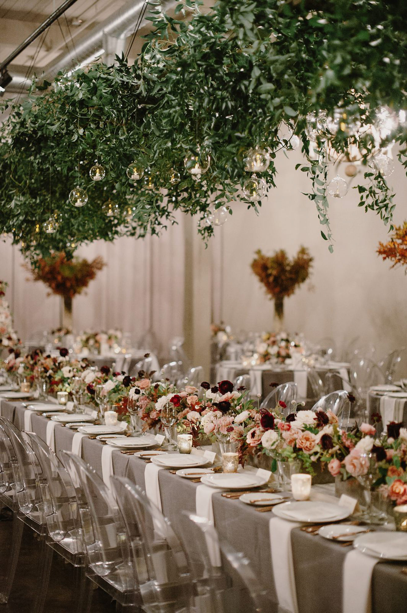 Greenery draped decor ghost chairs - photo by Kristen Marie Parker