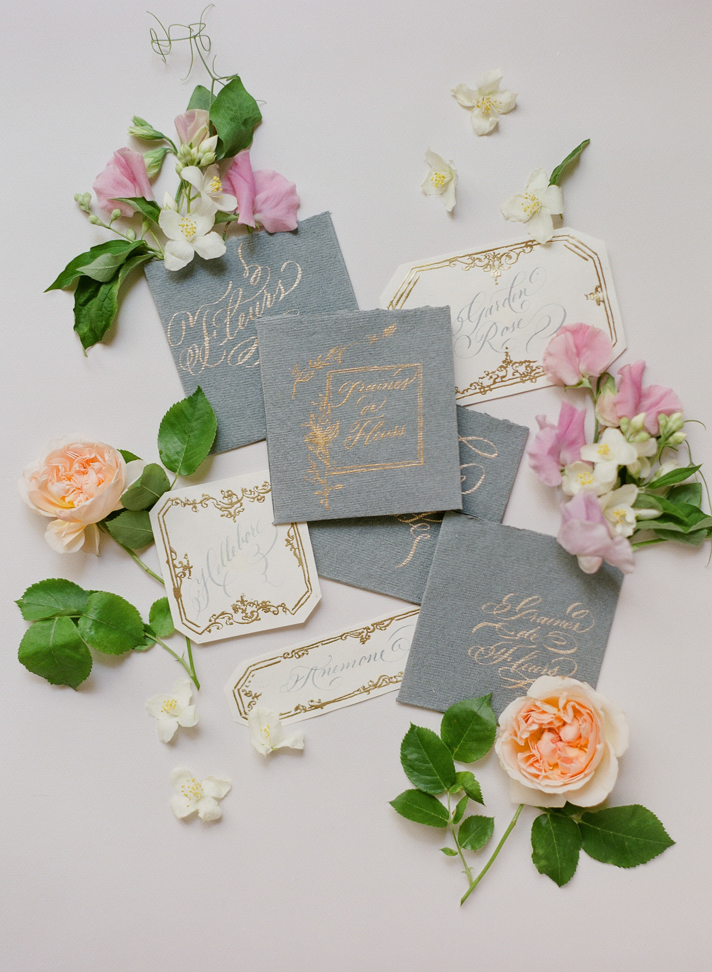 Flatlay of grey invitations with gold embossing and calligraphy - Greg Finck Photography