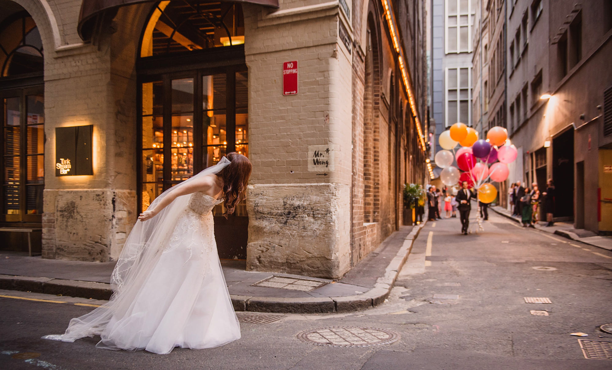 Bride peeks round corner to see groom coming with big balloons  -  Studio Impressions Photography