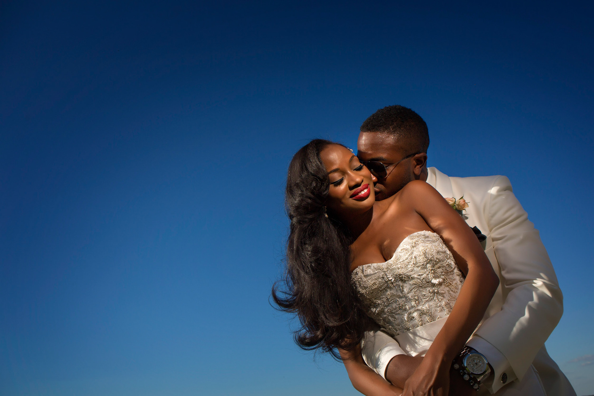 Groom and bride with beaded bodice - photo by Alakija Studios