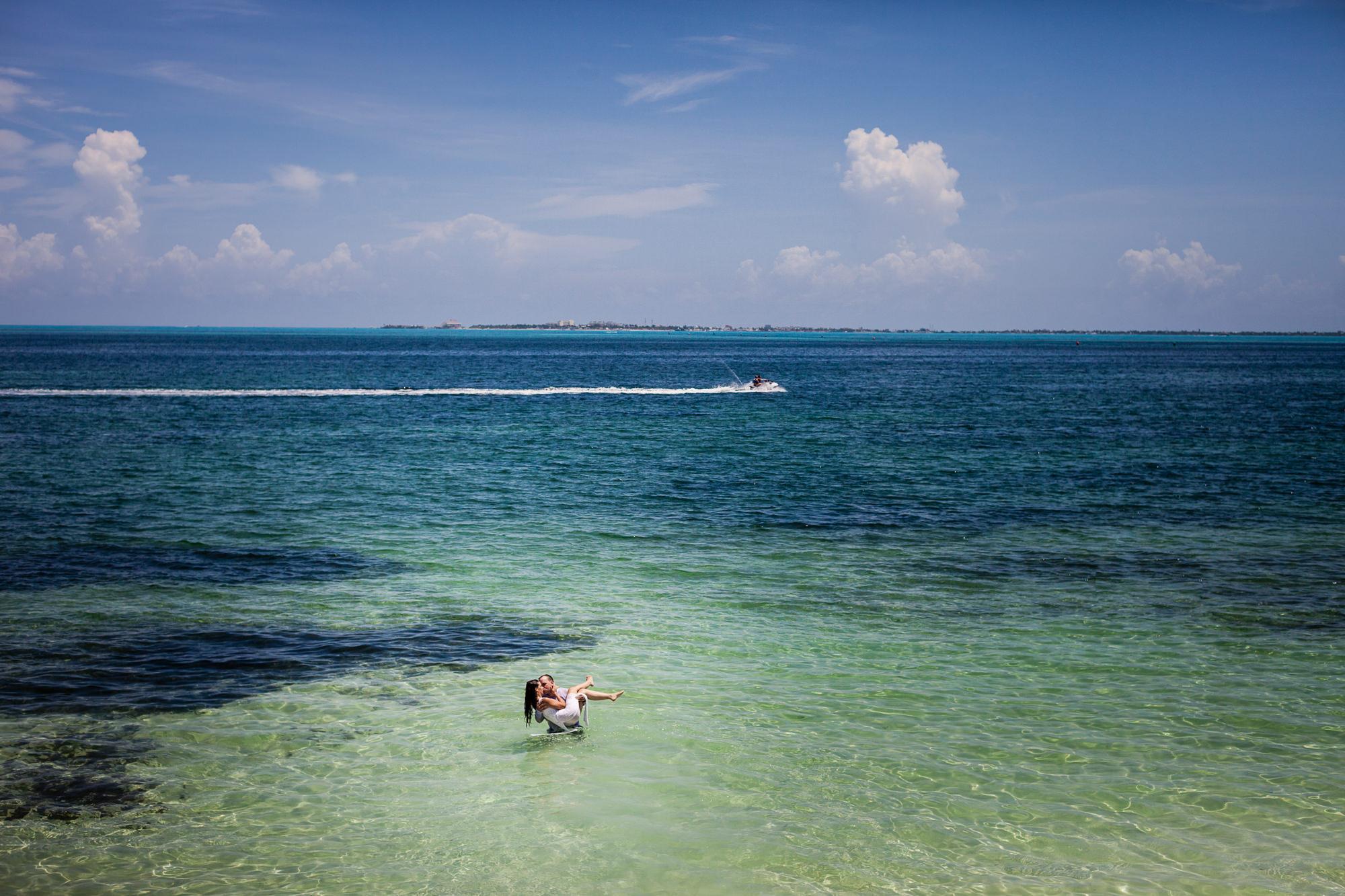 Groom carrying bride in the ocean - photo by Jag Studios