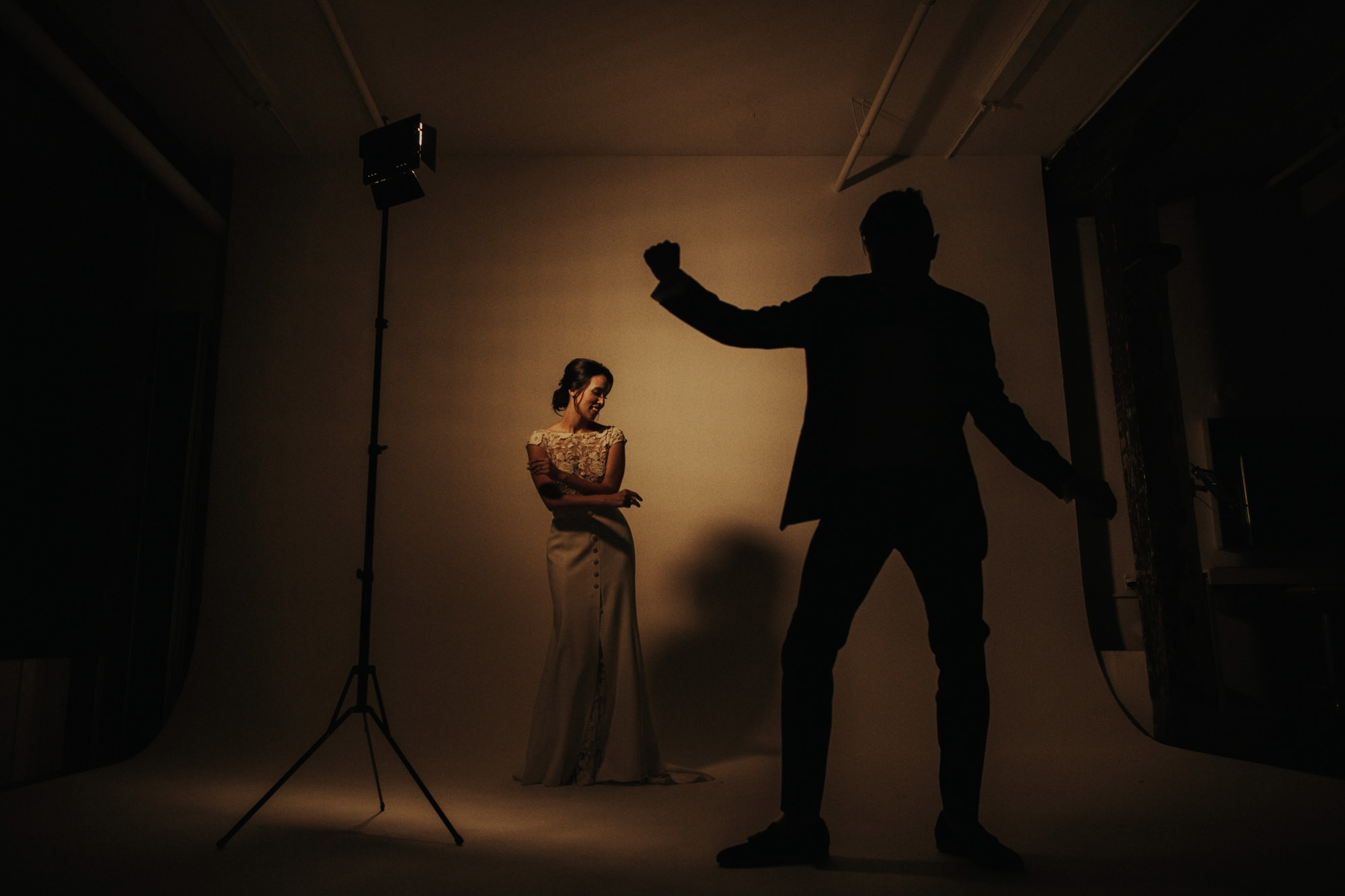 Silhouette of groom dancing and bride smiling in studio -  photo by Dan O'Day