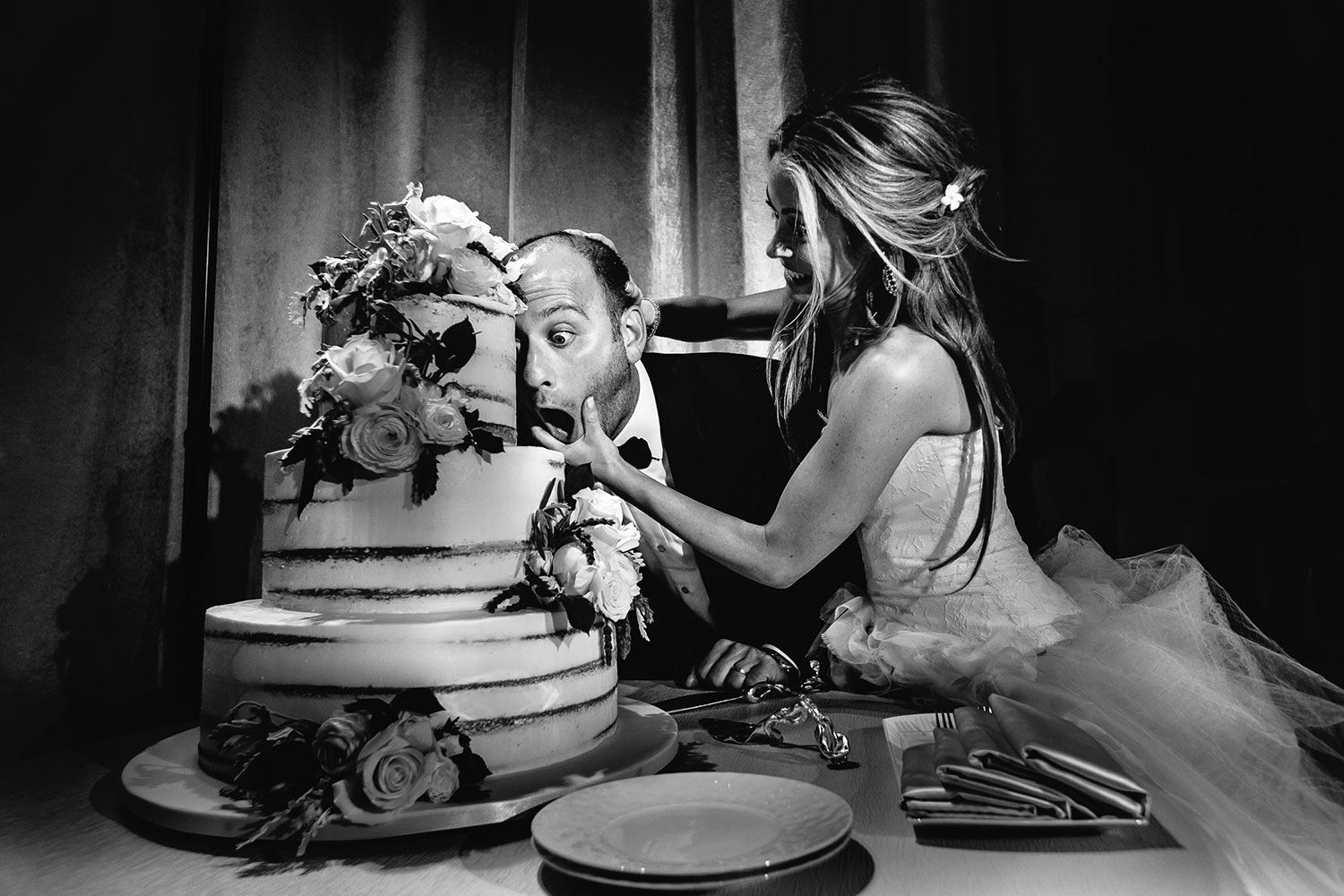 Funny bride forcing groom to take bite of cake, by Calloway Gable