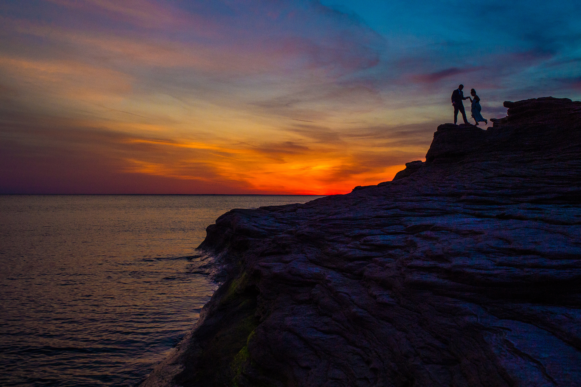 Bride and groom on cliff with electric sunset - photo by Cooked Photography