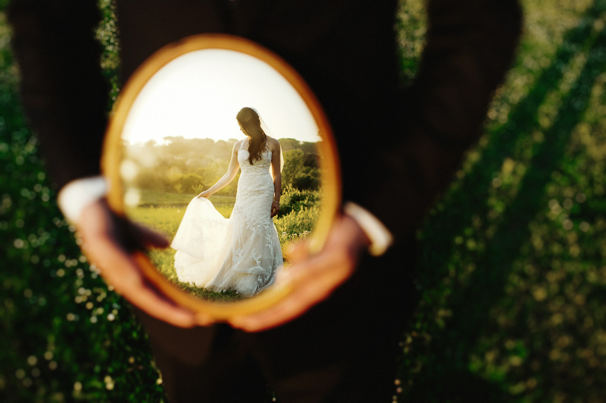 Groom holding mirror with bride reflected - photo by Fer Juaristi