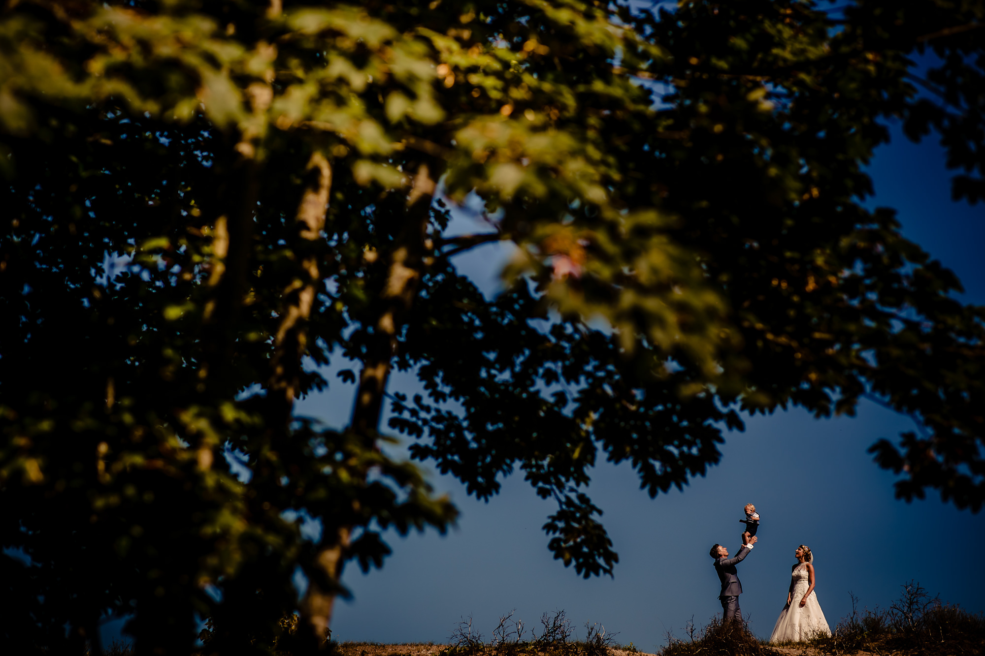 bride with groom holding their baby above his head photo by Eppel Photography