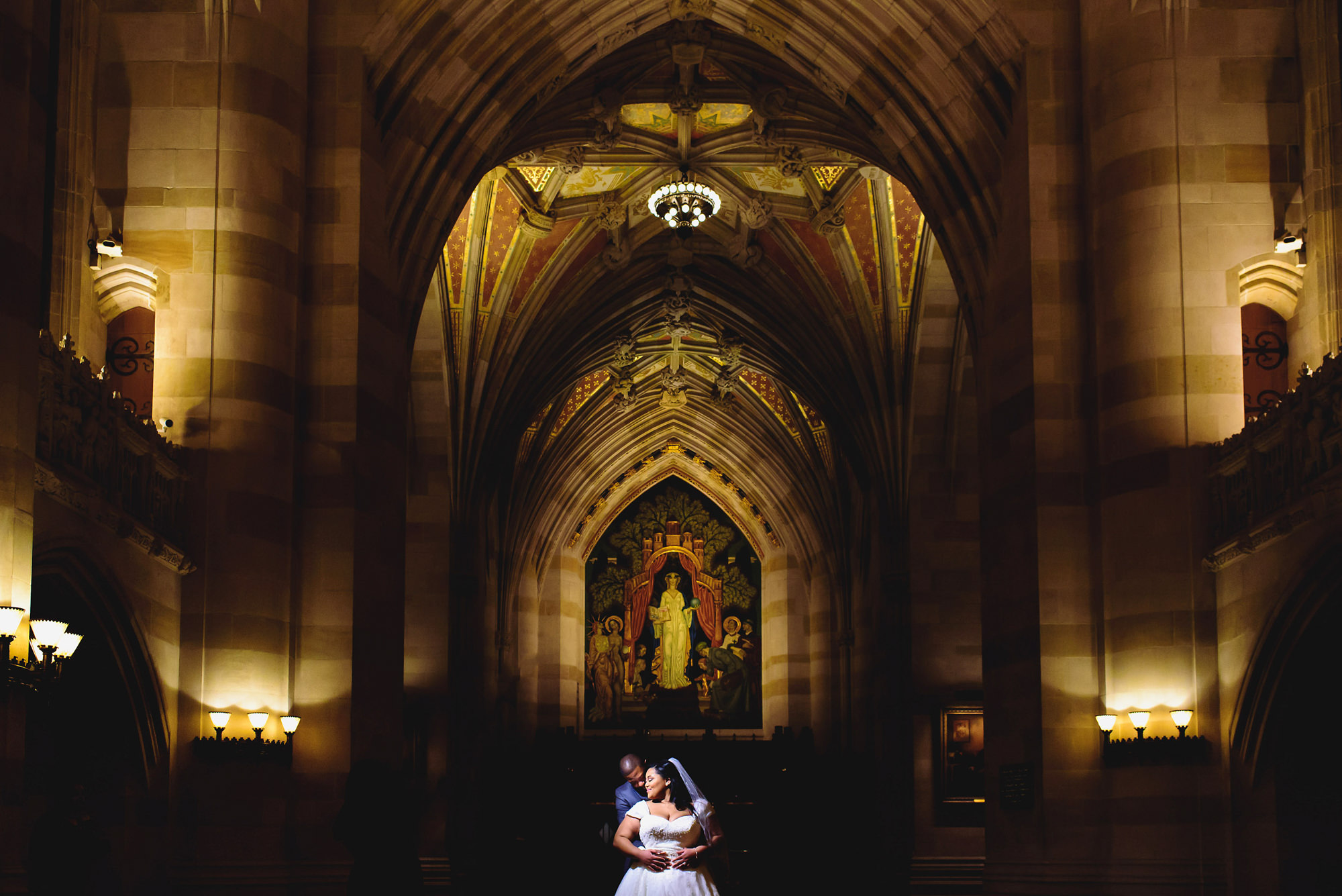Groom hugs ride in gothic cathedral - photo by Alakija Studios