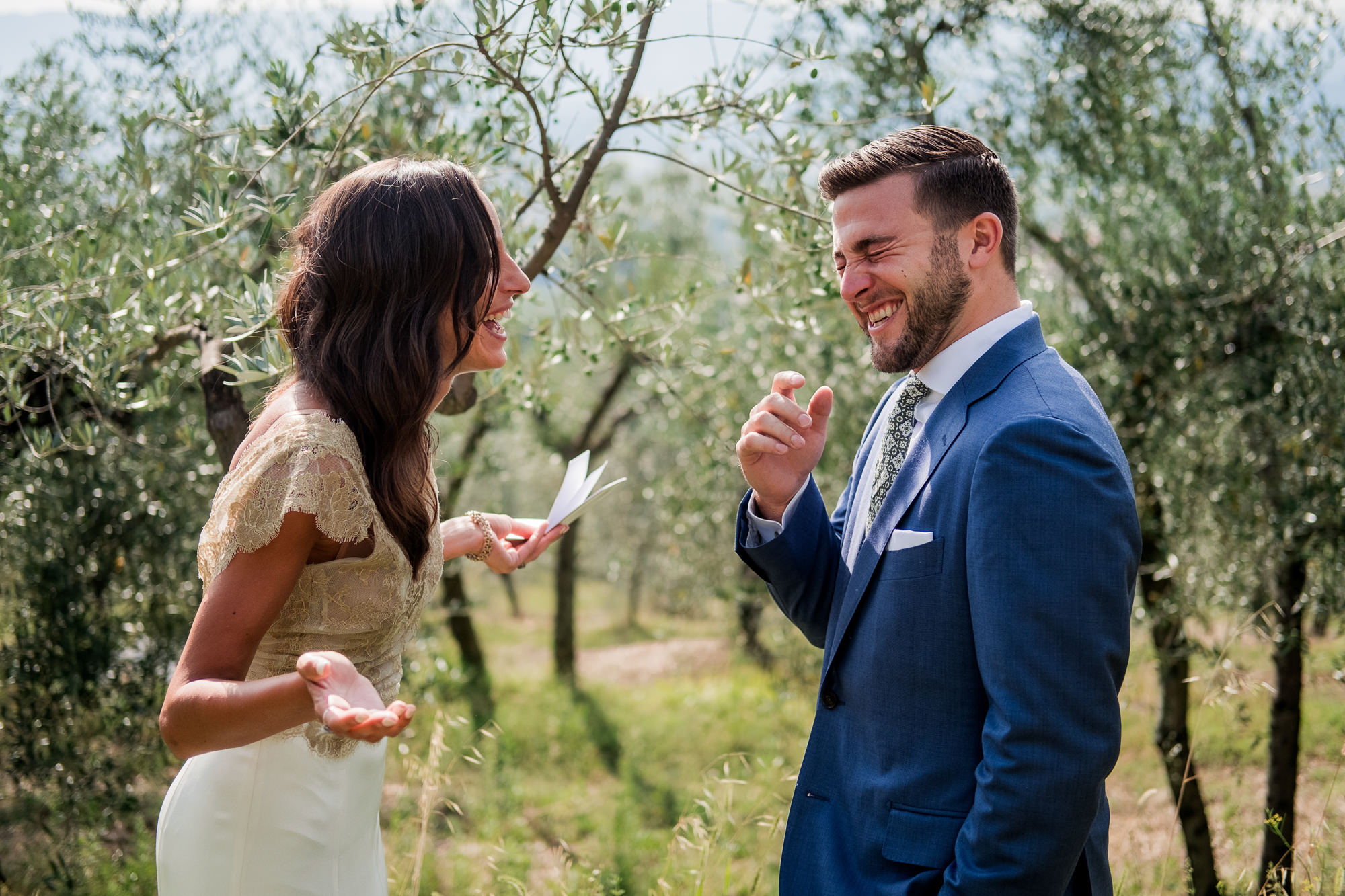 Groom in blue suit laughs as bride reads vows photo by Nordica Photography