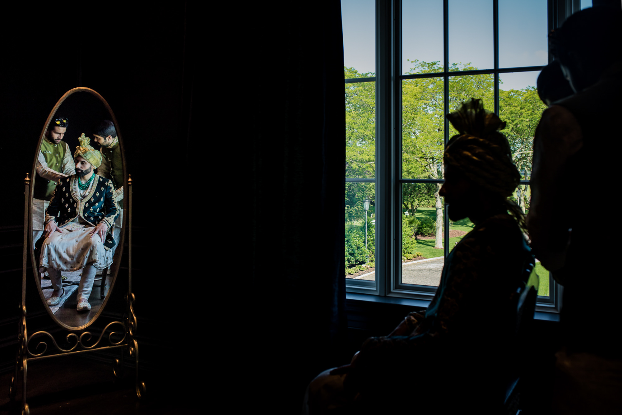 Indian groom in green gold attire reflected in mirror - photo by RImi Sen Photography