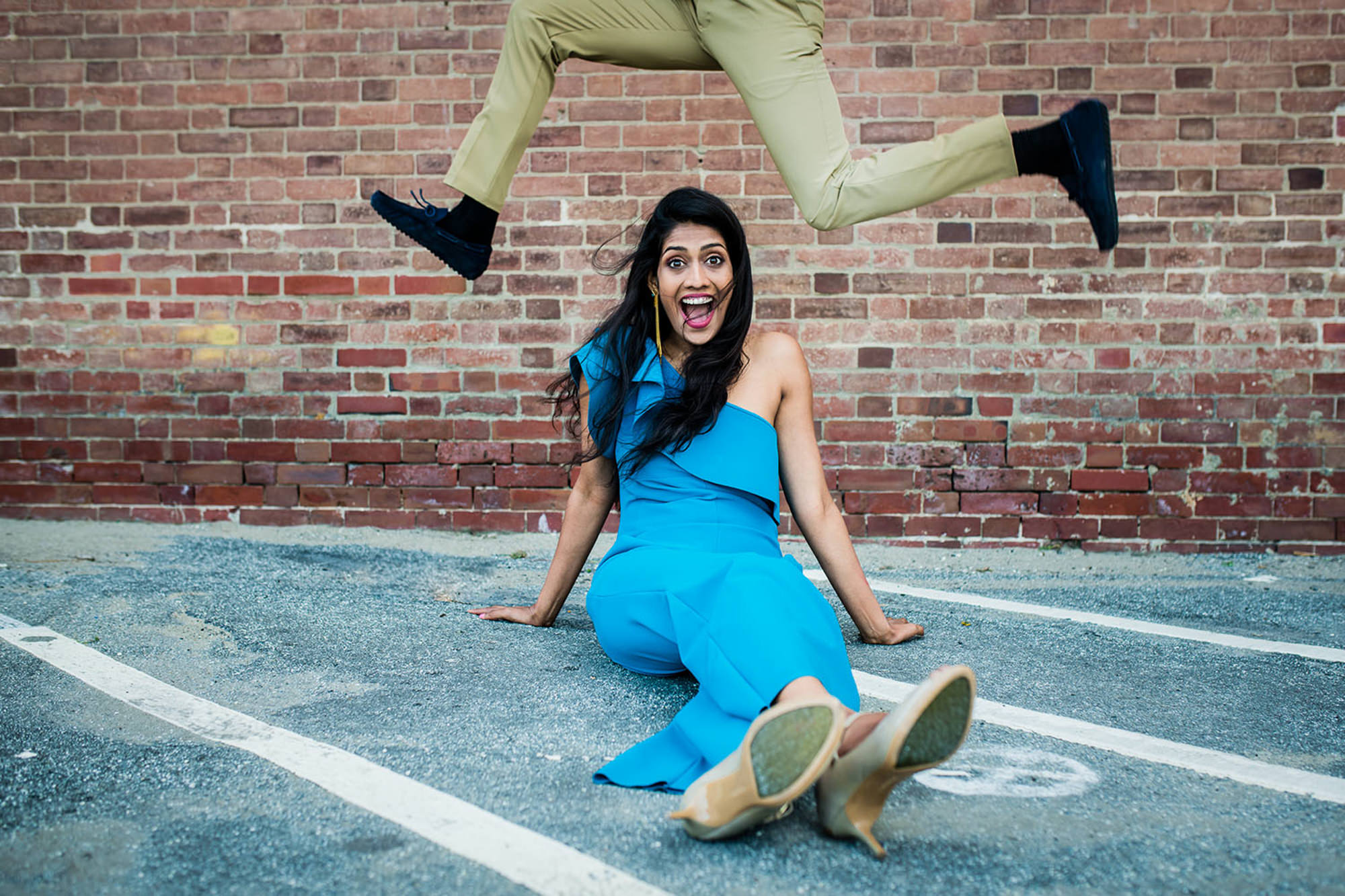 Groom jumping over bride in blue outfit photo by Rimi Sen