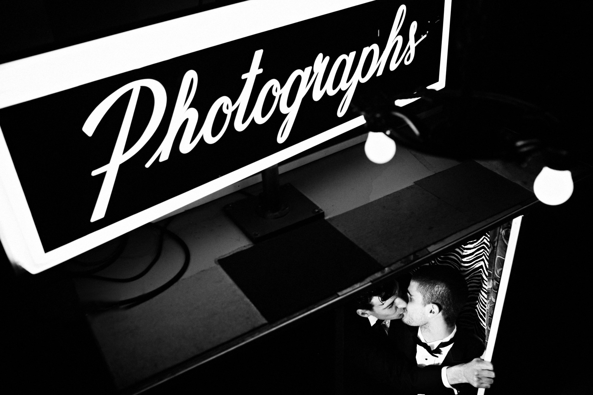 Grooms kiss in photo booth - PhotoJJ