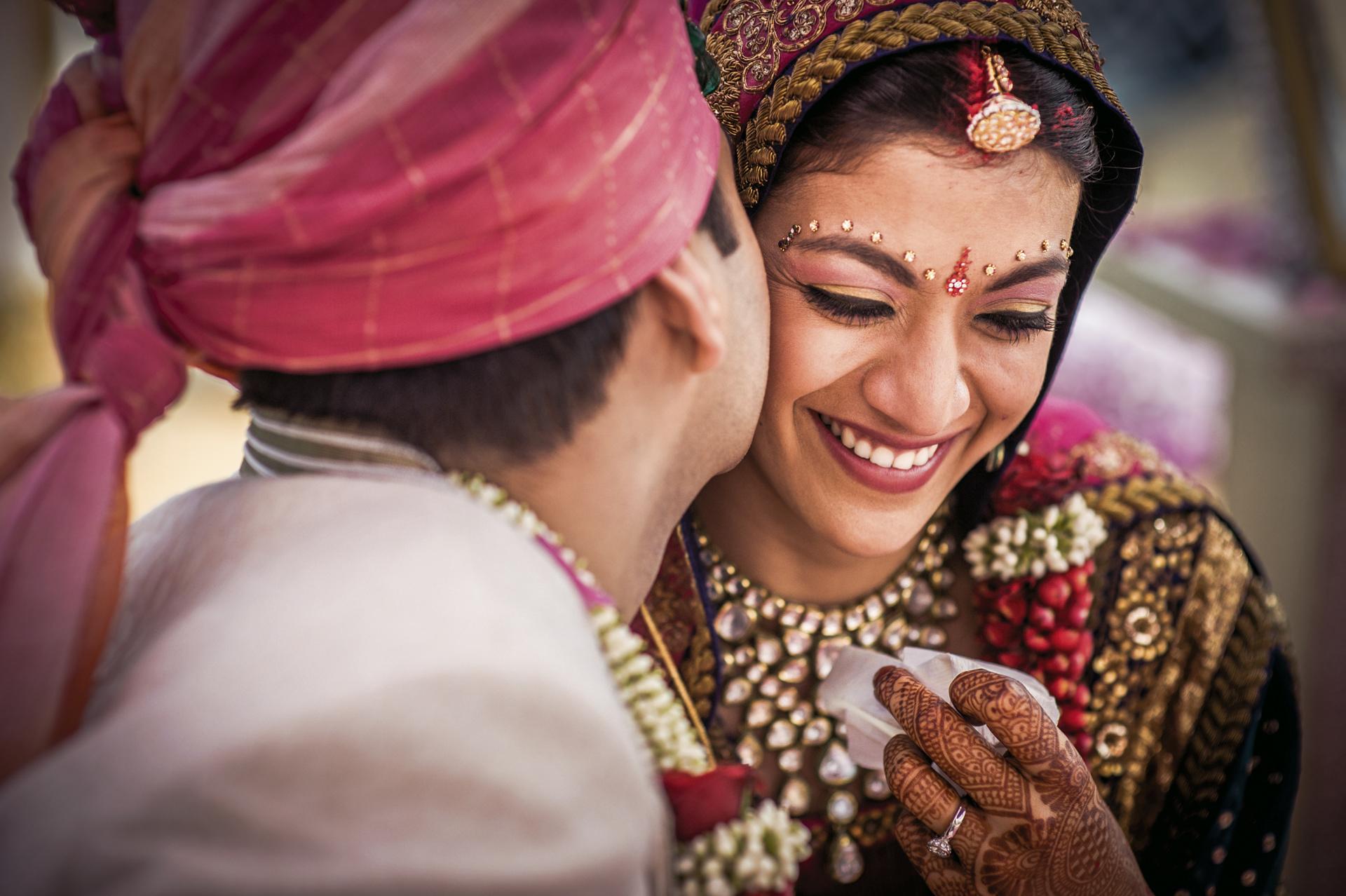 Indian groom kisses bride on cheek by Sephi Bergerson Bengaluru