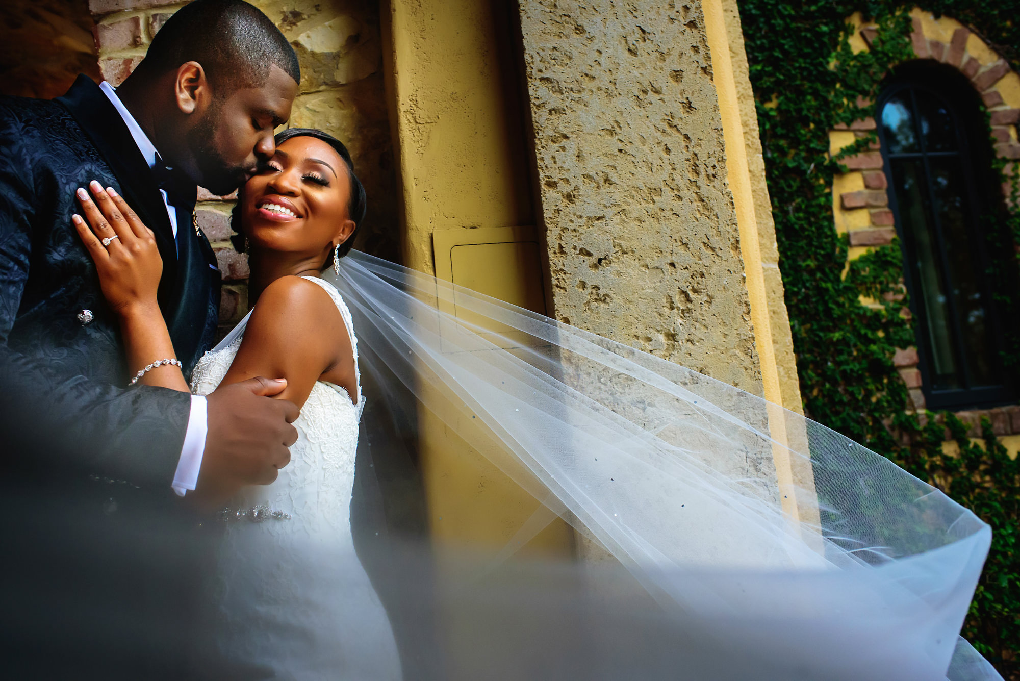 Groom kisses bride in swirling veil - photo by Alakija Studios