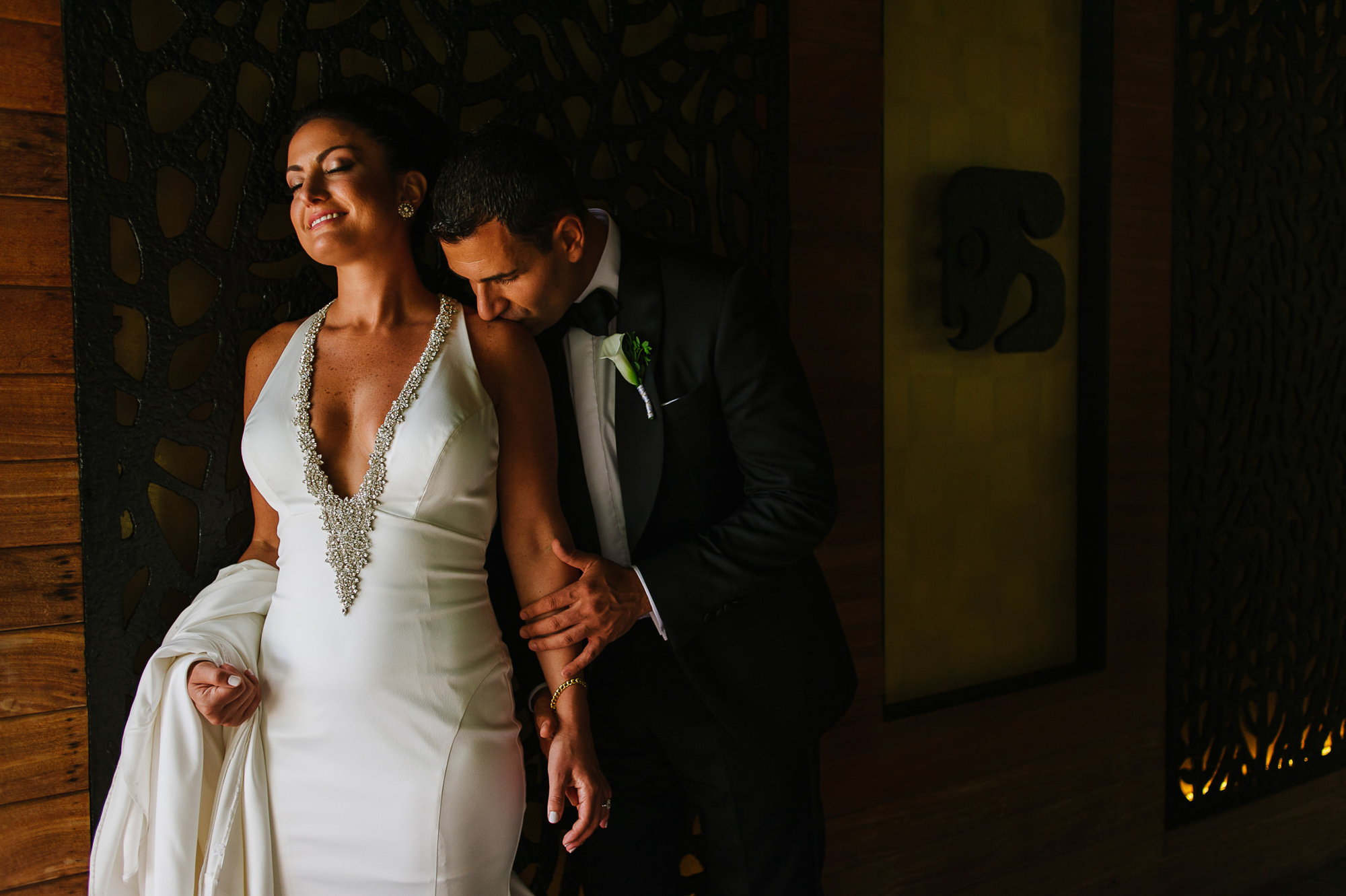 Groom kisses bride in plunging neckline satin gown, by Citlalli Rico