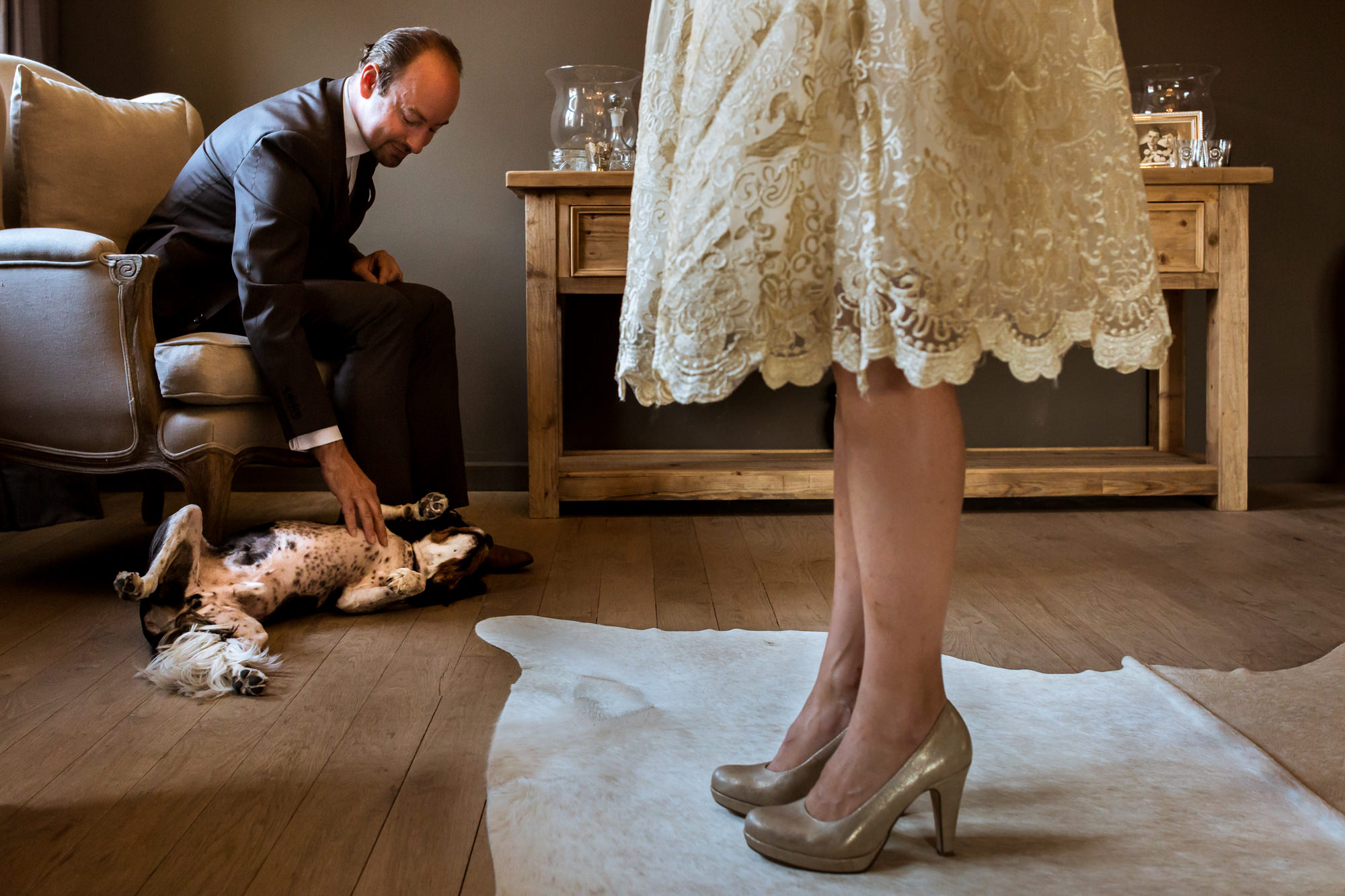 Groom plays with dog as bride looks on photo by Fotobelle: Isabelle Hattink