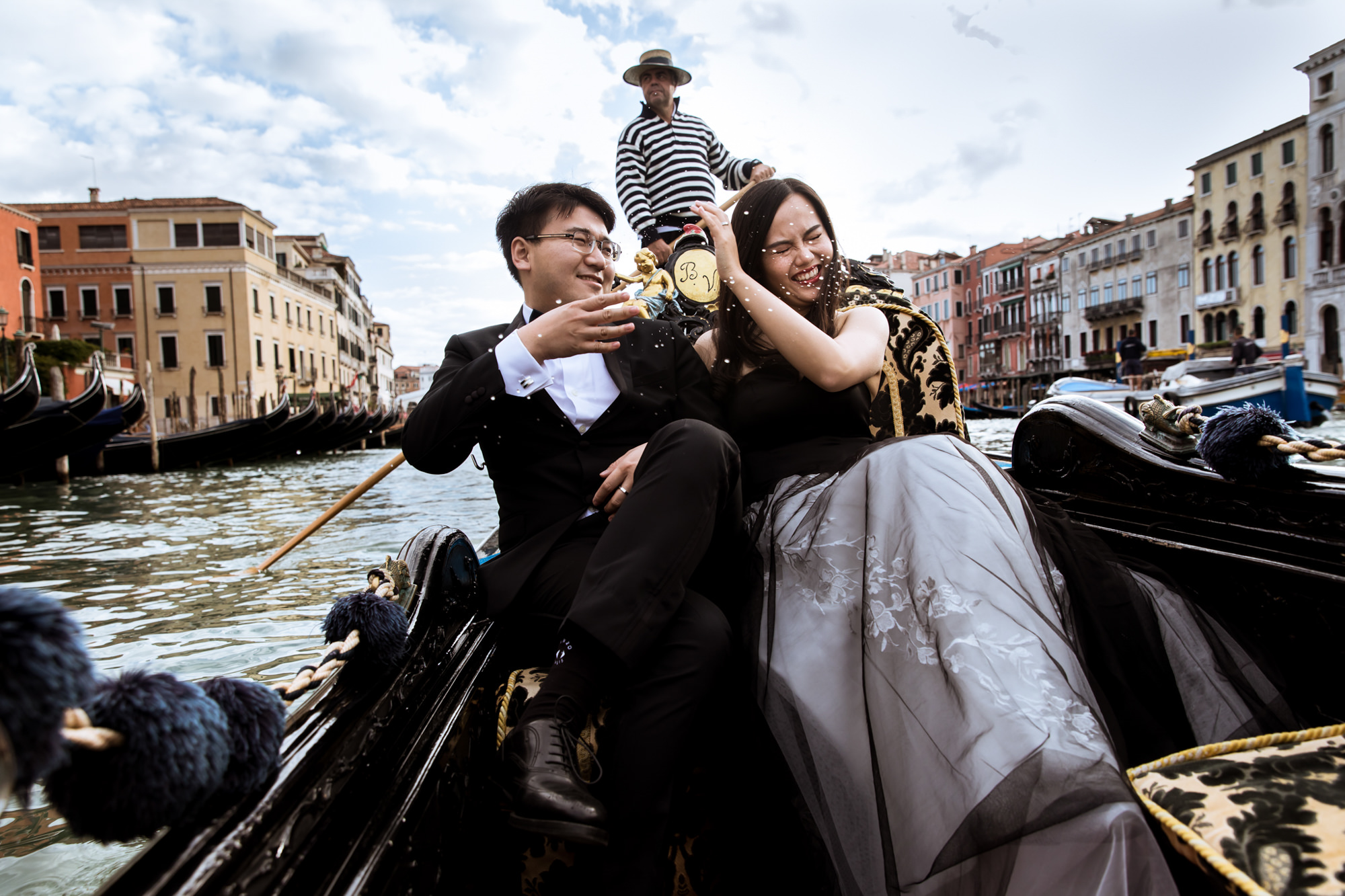 Groom splashing bride on Gondola Ride photo by Fotobelle: Isabelle Hattink