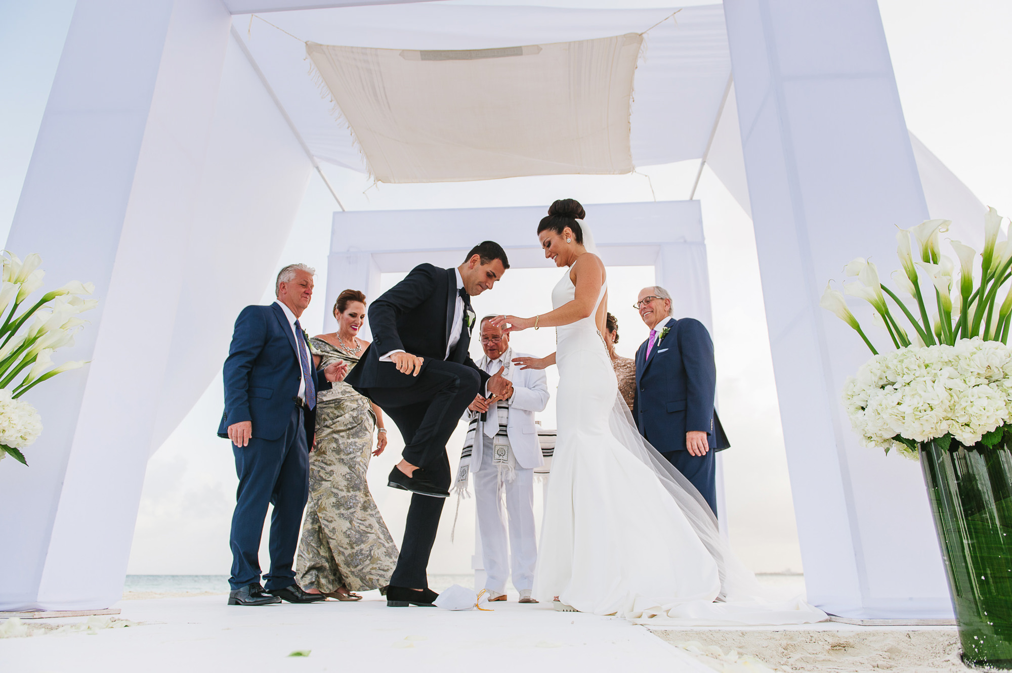 Groom stepping on glass for Jewish wedding ceremony under white chuppah, by Citlalli Rico