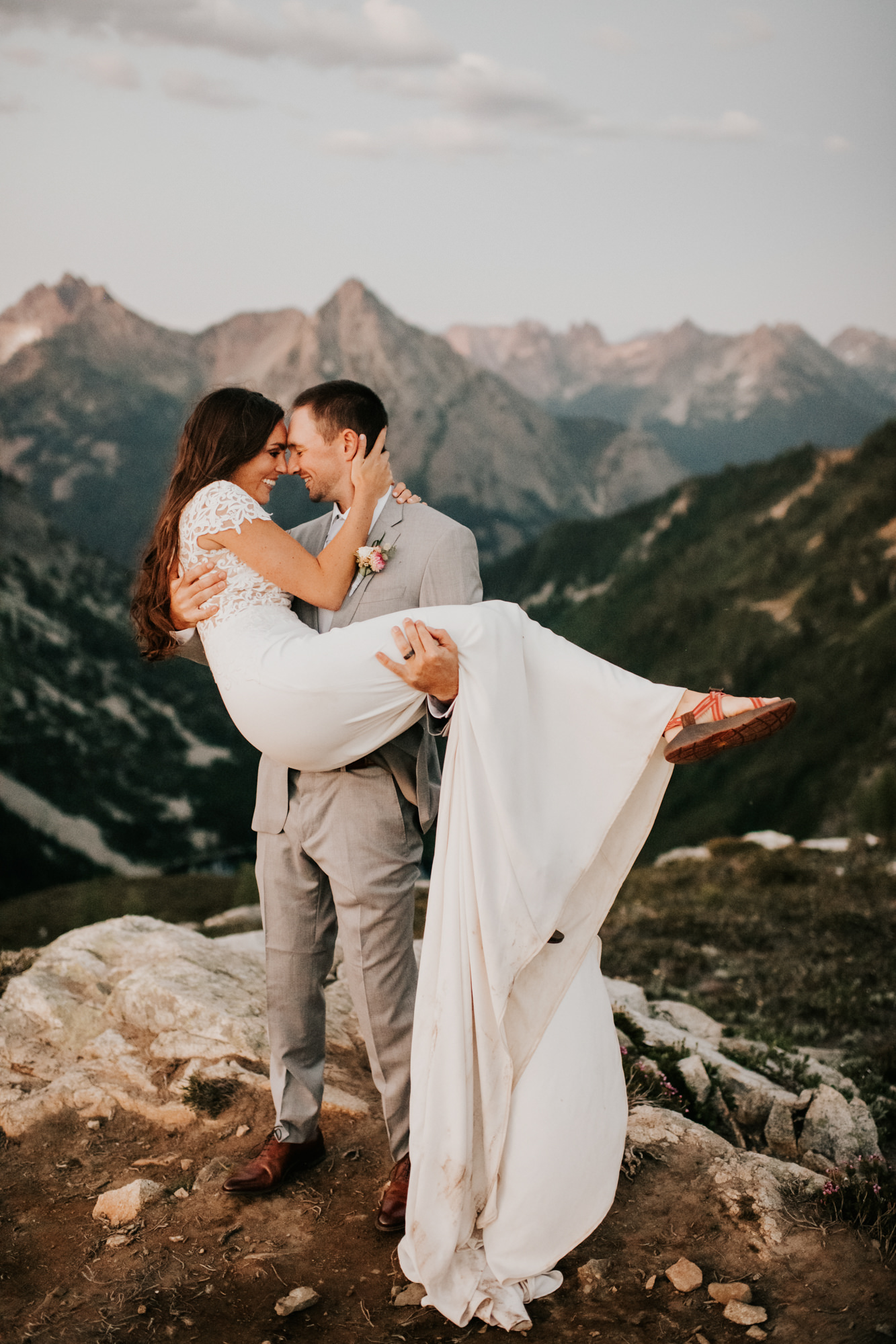 Bride in lace dress swept off feet by groom in grey suit- photo by Nick + Danee