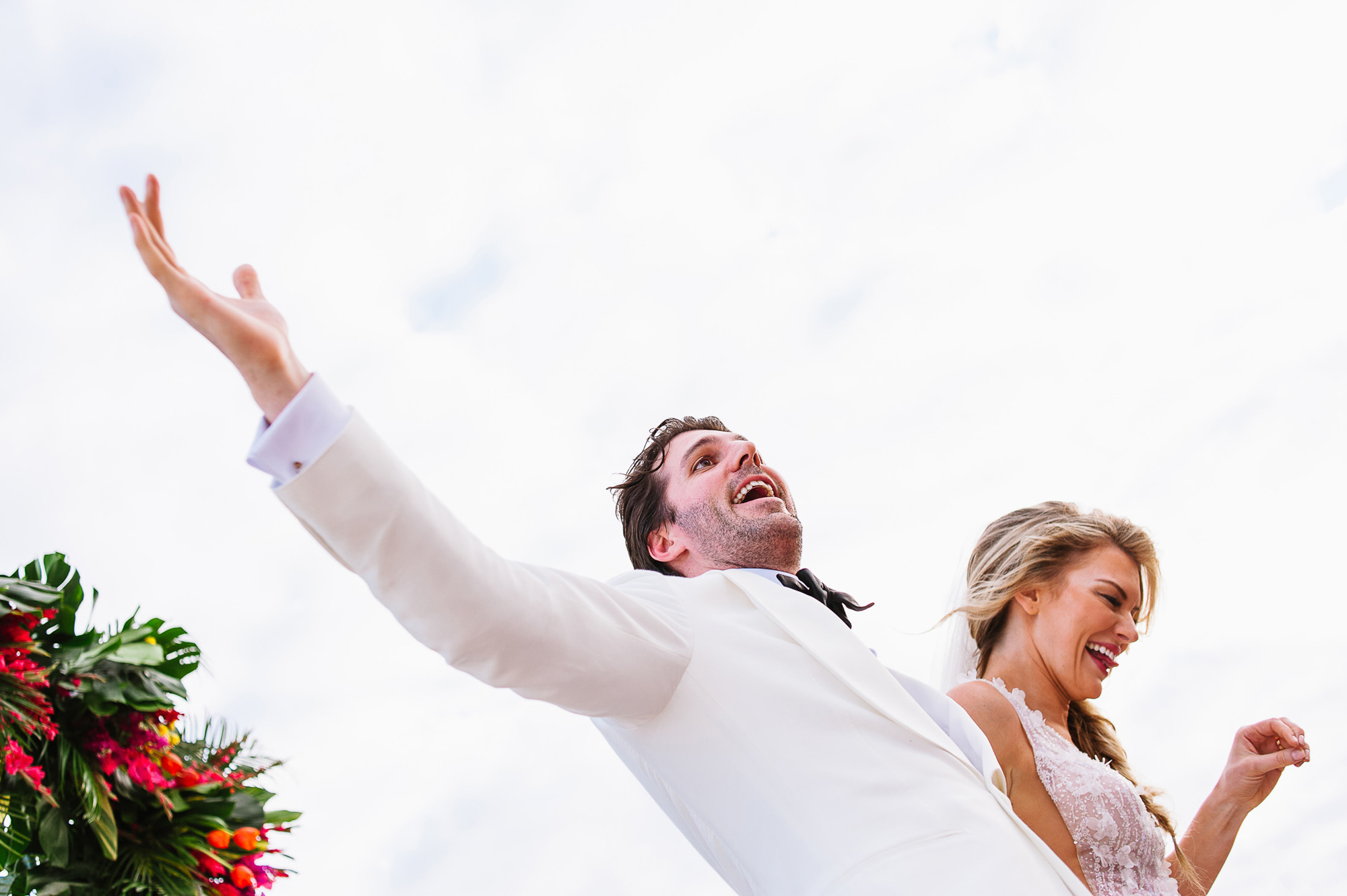 Groom in white tuxedo and bride cheer before walking down the aisle, by Citlalli Rico