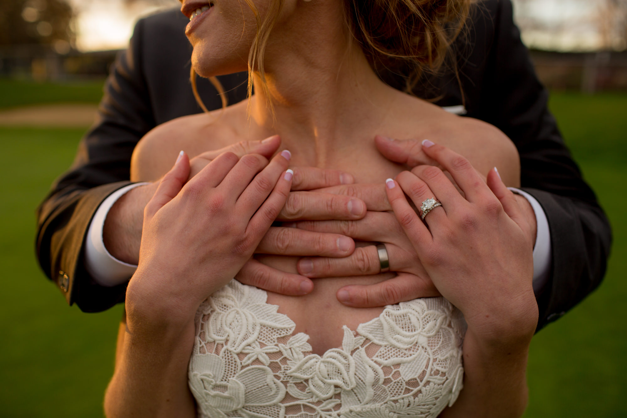 Groom hands around bride with wedding rings - Jessica Hill Photography