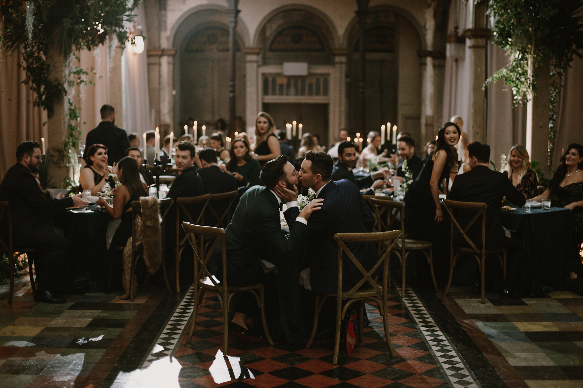 Grooms kiss one another at elegant tiled venue - photo by Kristen Marie Parker