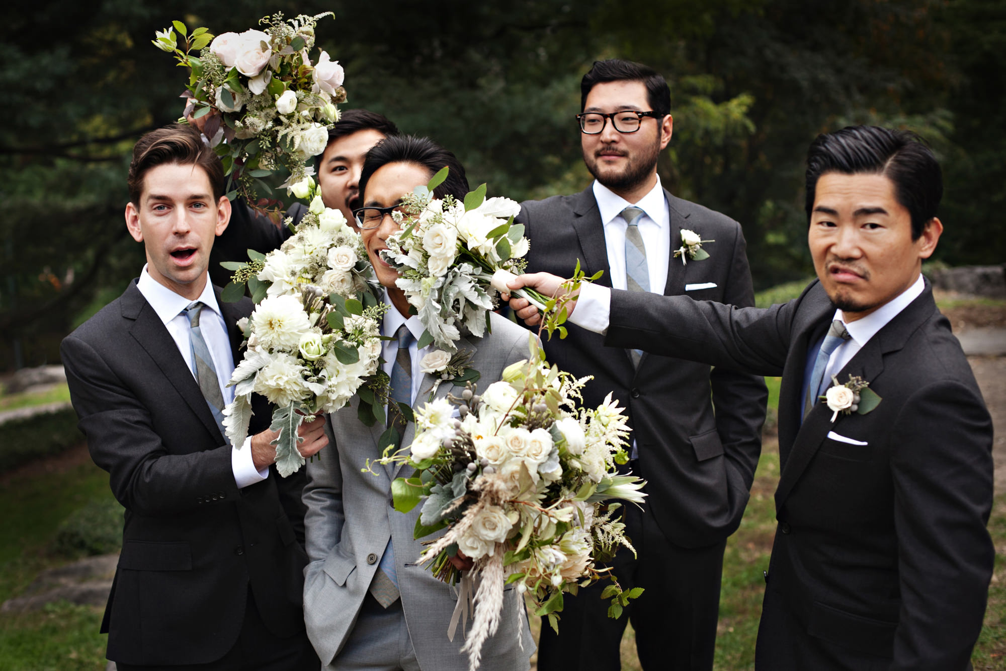 Groomsman pushes white rose bouquet into grooms face - PhotoJJ